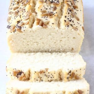 A loaf of coconut flour bread topped with sunflower seeds and poppy seeds with two slices next to it