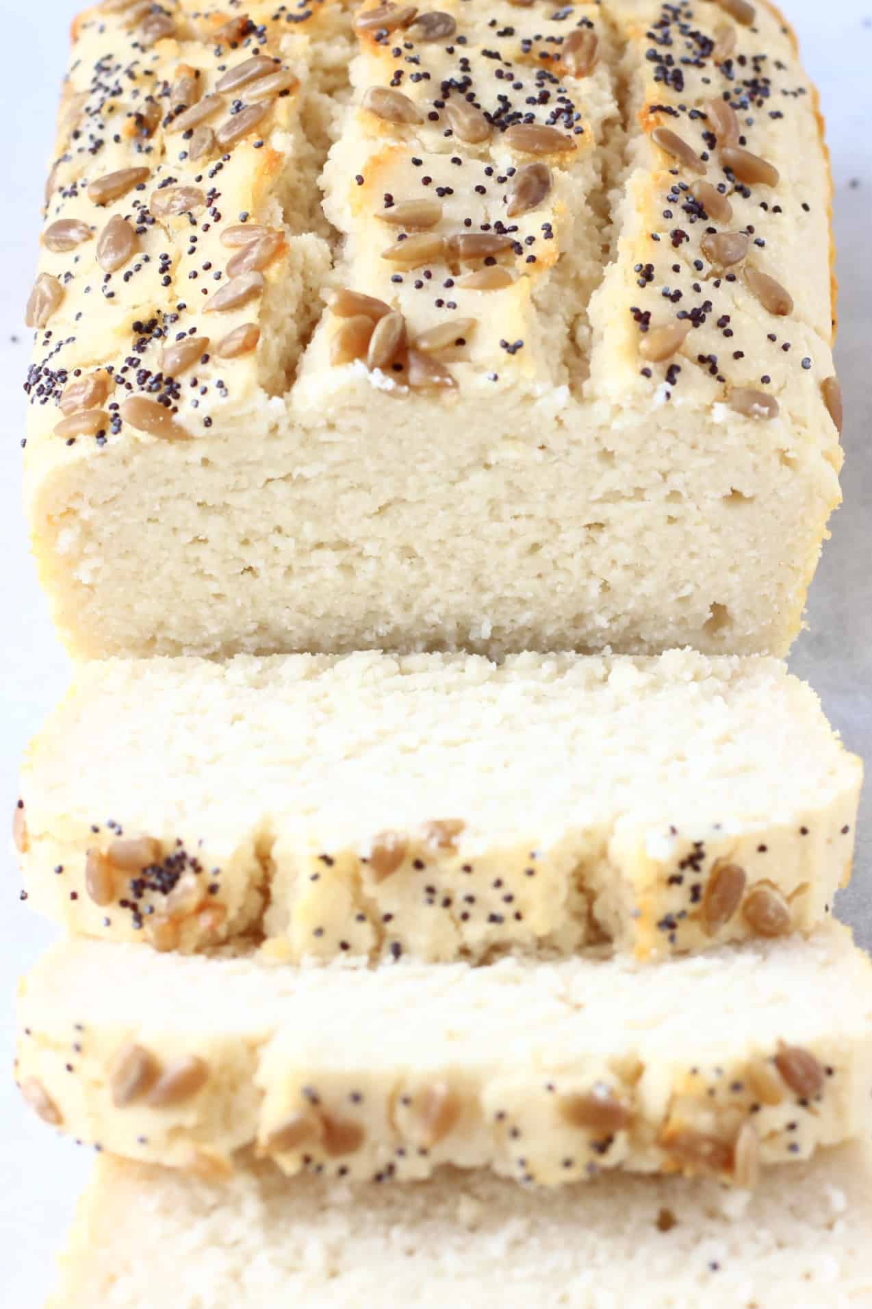 A loaf of coconut flour bread topped with sunflower seeds and poppy seeds with three slices next to it