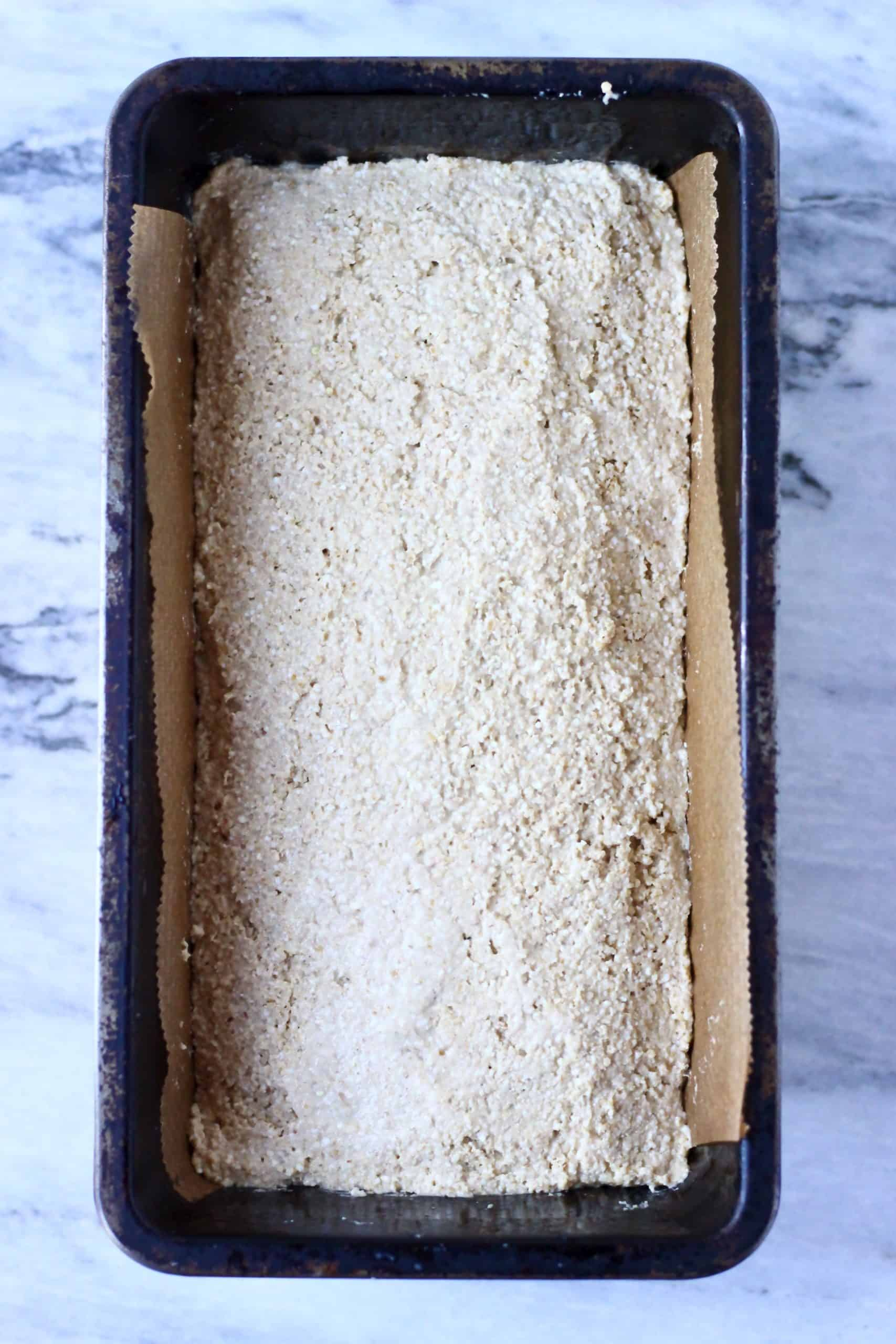 Quinoa bread batter in a loaf tin lined with baking paper
