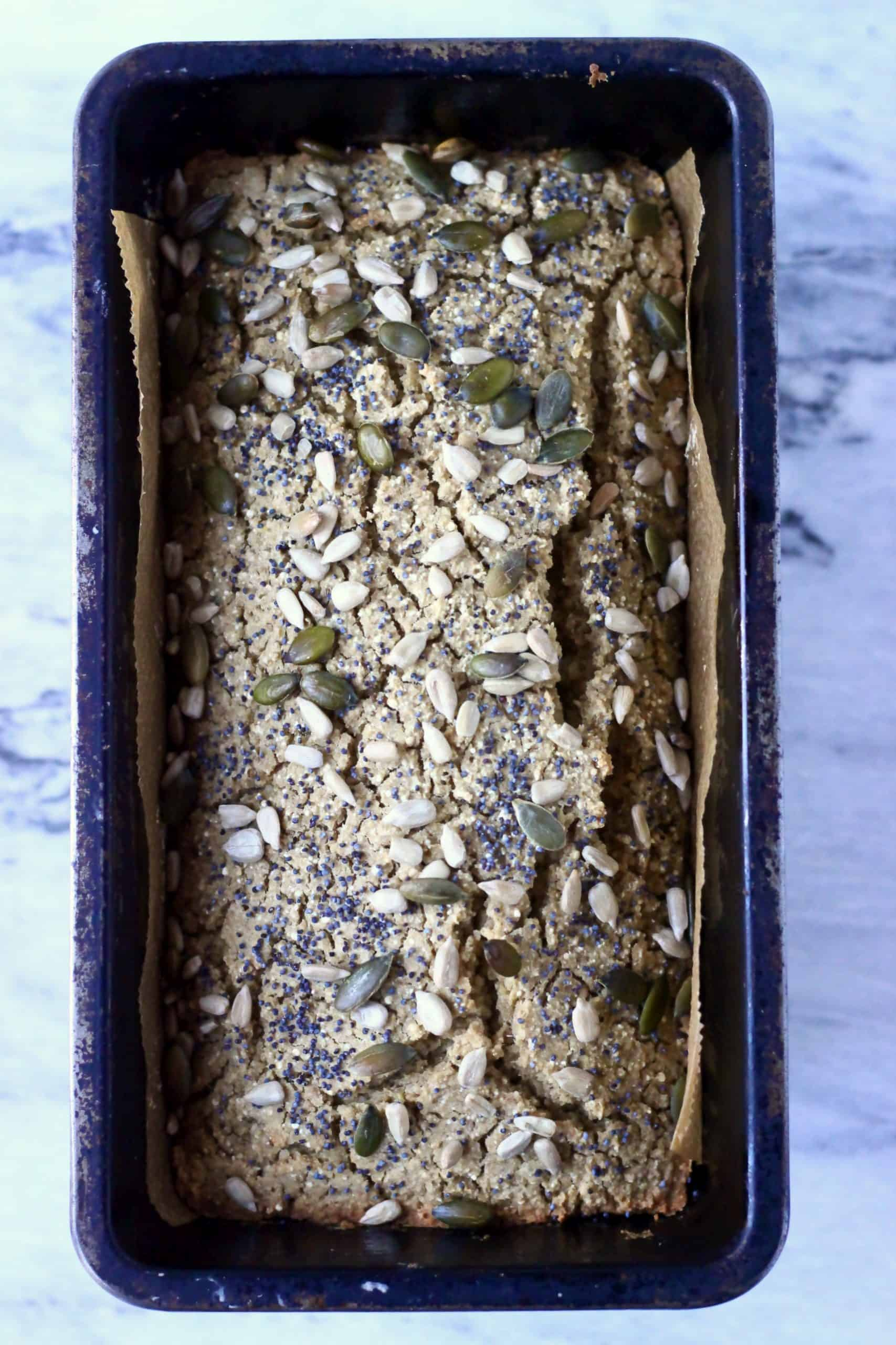 Quinoa bread topped with mixed seeds in a loaf tin lined with baking paper