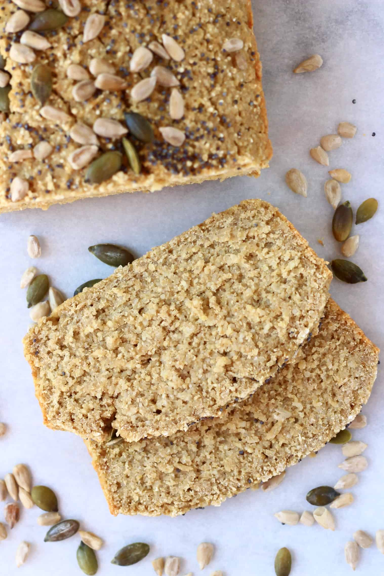 A loaf of quinoa bread topped with seeds with two slices next to it
