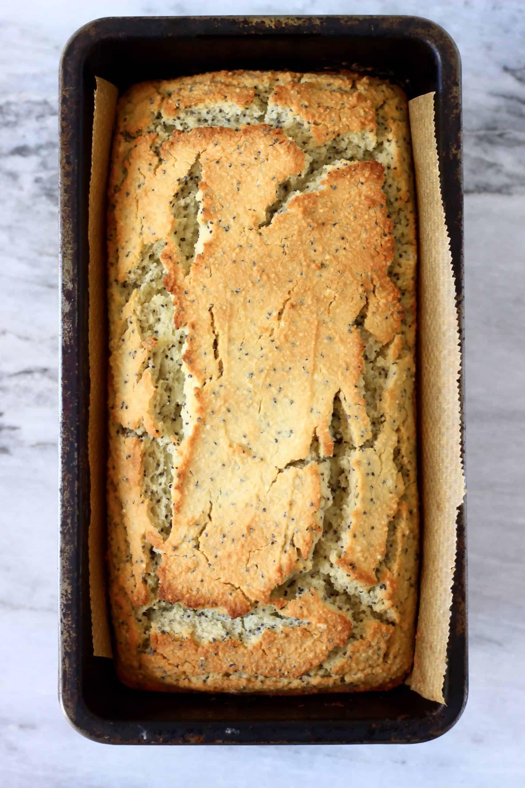 A loaf of gluten-free vegan lemon poppy seed bread in a loaf tin