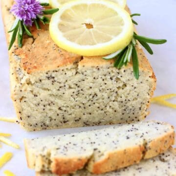 A loaf of gluten-free vegan lemon poppy seed bread with two slices next to it topped with lemon slices