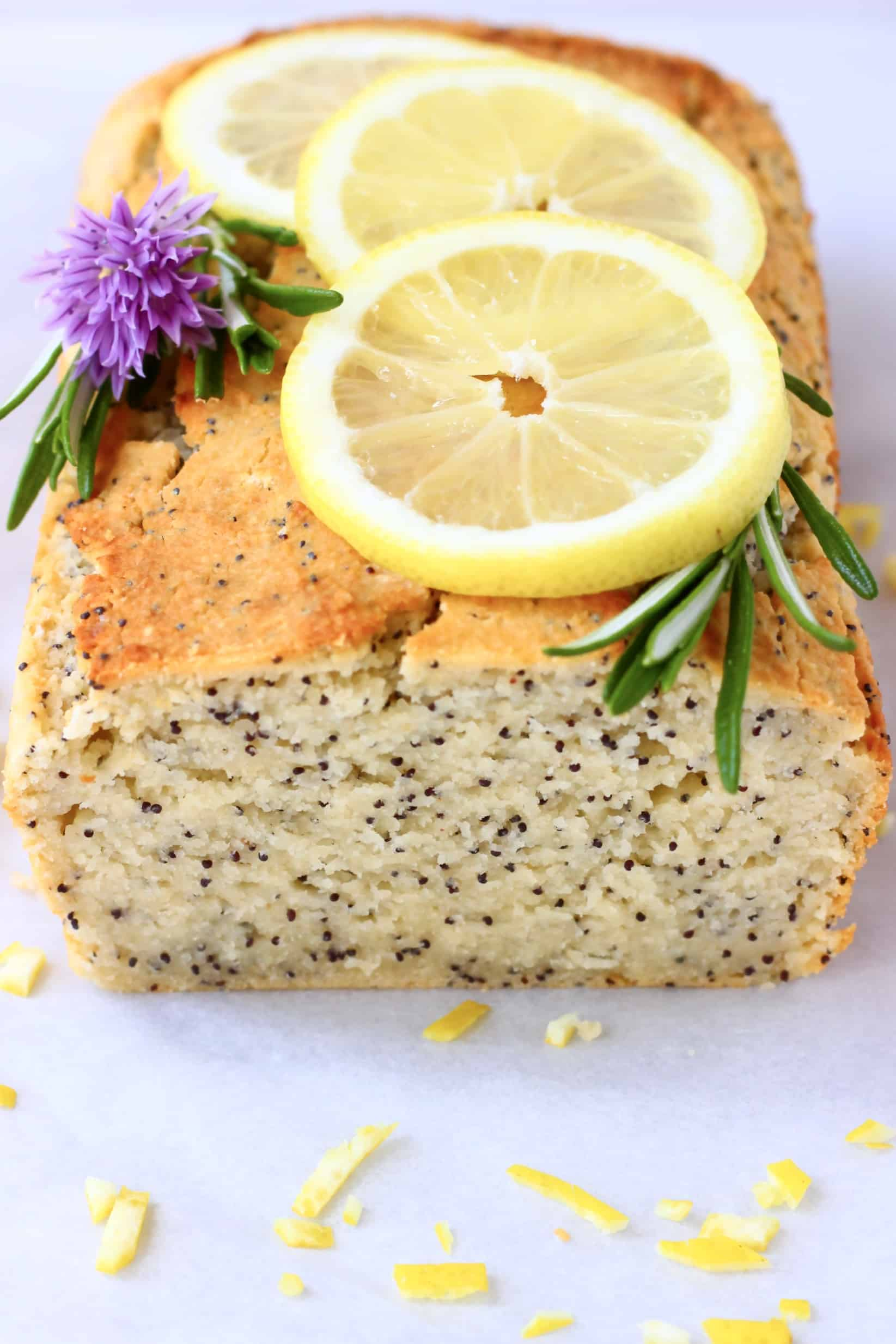 A loaf of gluten-free vegan lemon poppy seed bread topped with lemon slices