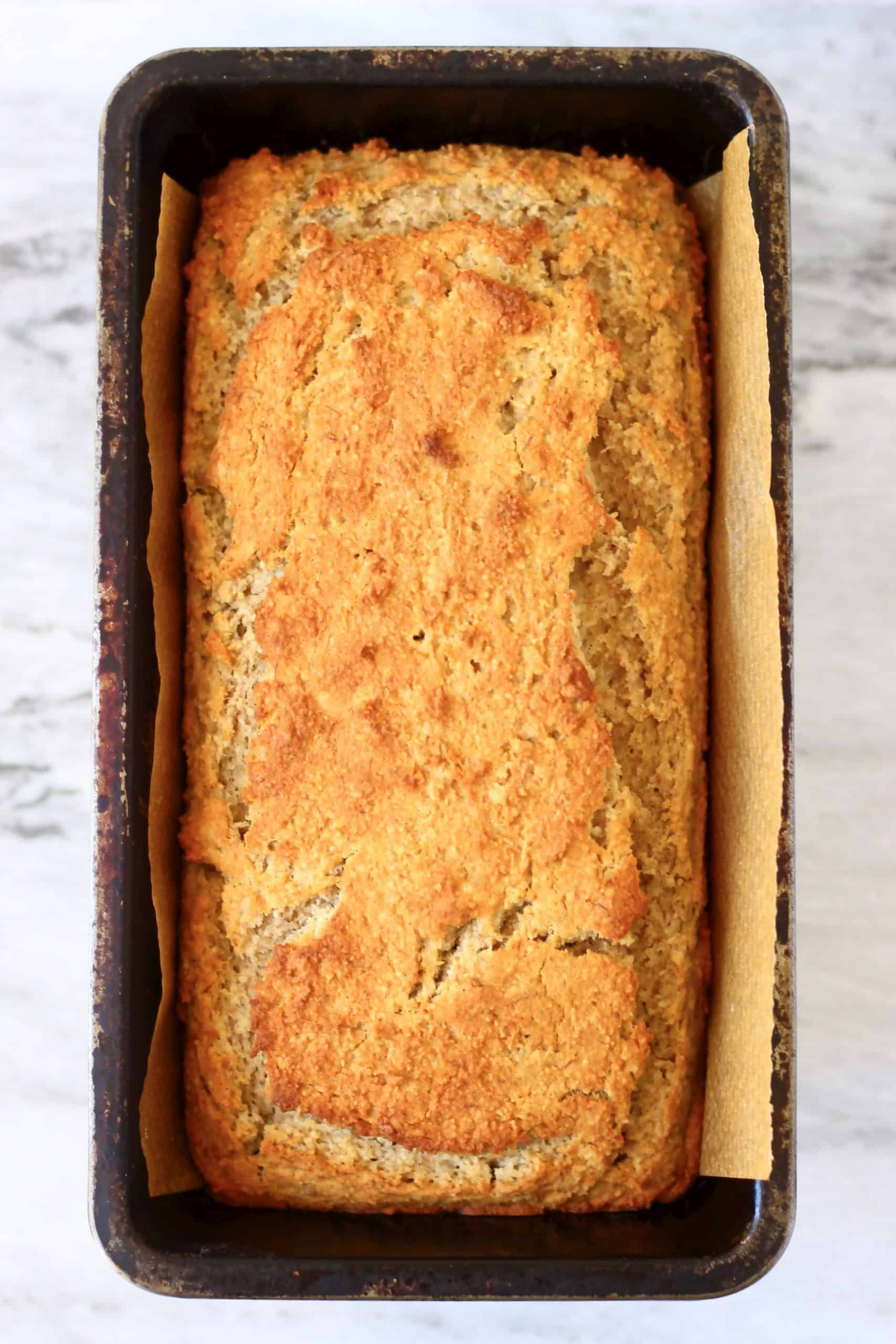A loaf of gluten-free vegan peanut butter banana bread in a loaf tin