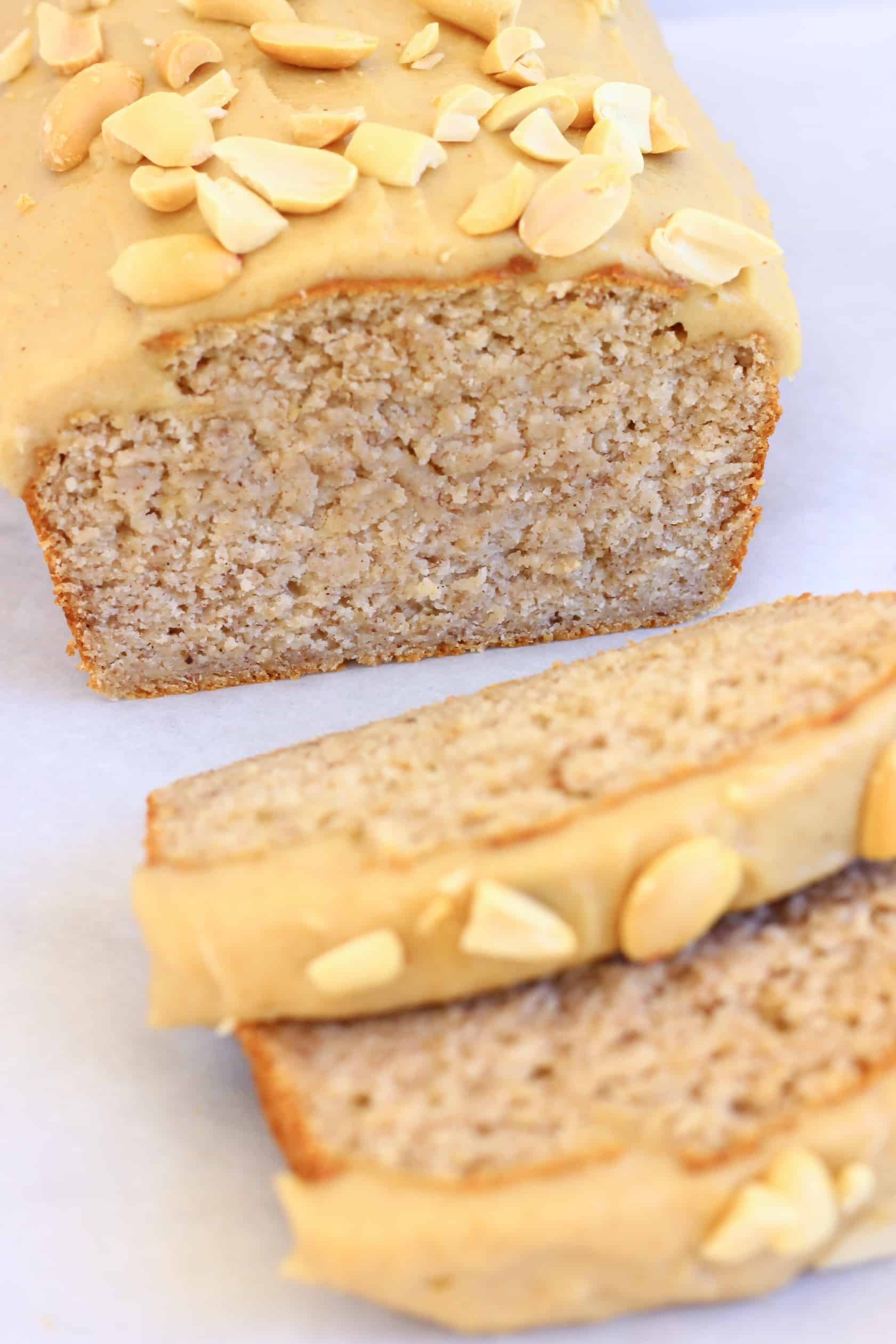 A loaf of gluten-free vegan peanut butter banana bread with peanut butter frosting with two slices next to it