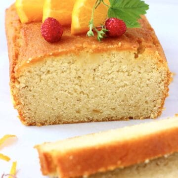 A loaf of gluten-free vegan orange drizzle cake topped with mini strawberries and orange slices with two slices next to it