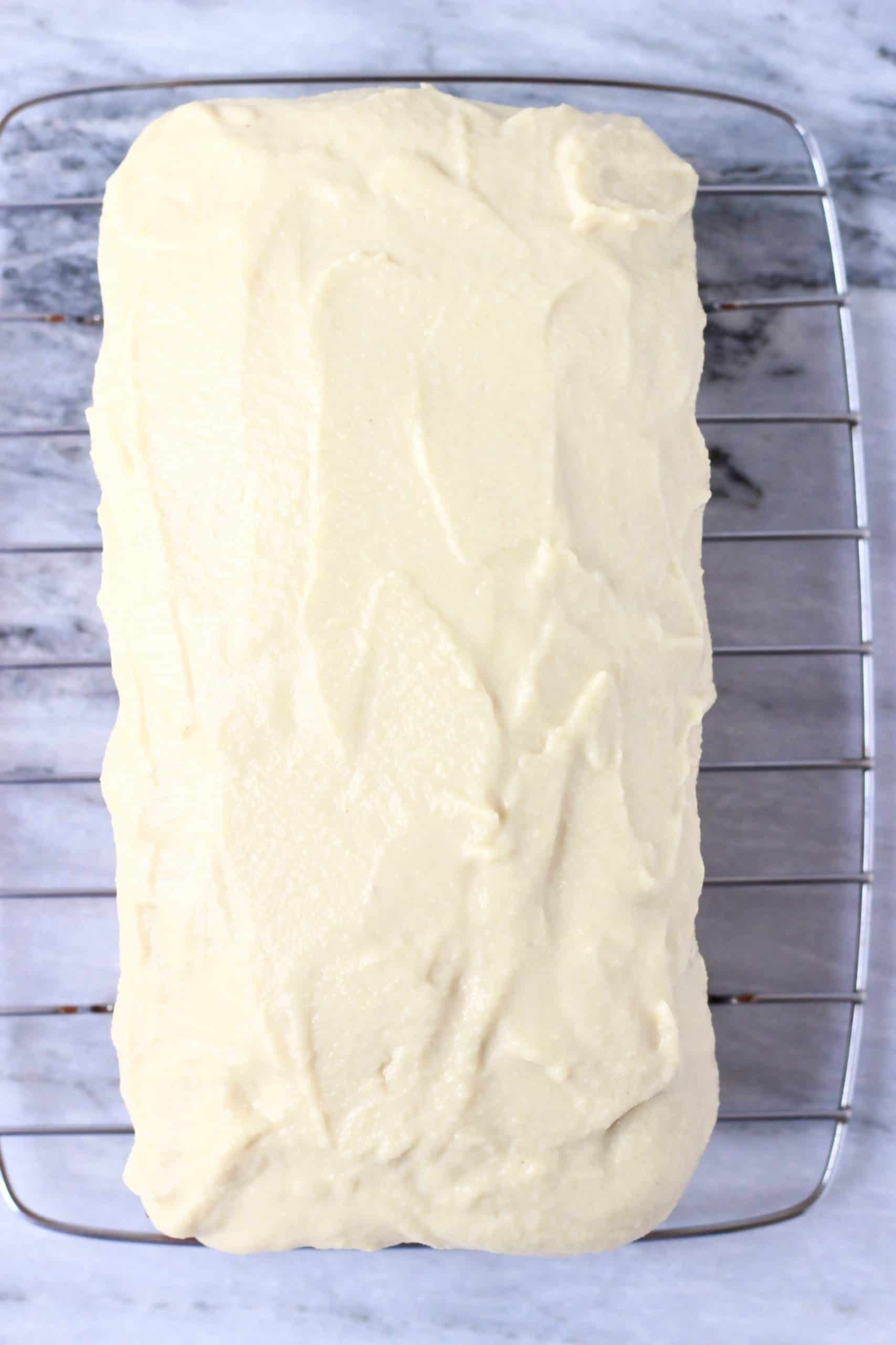 A loaf of gluten-free vegan lemon bread on a wire rack topped with frosting