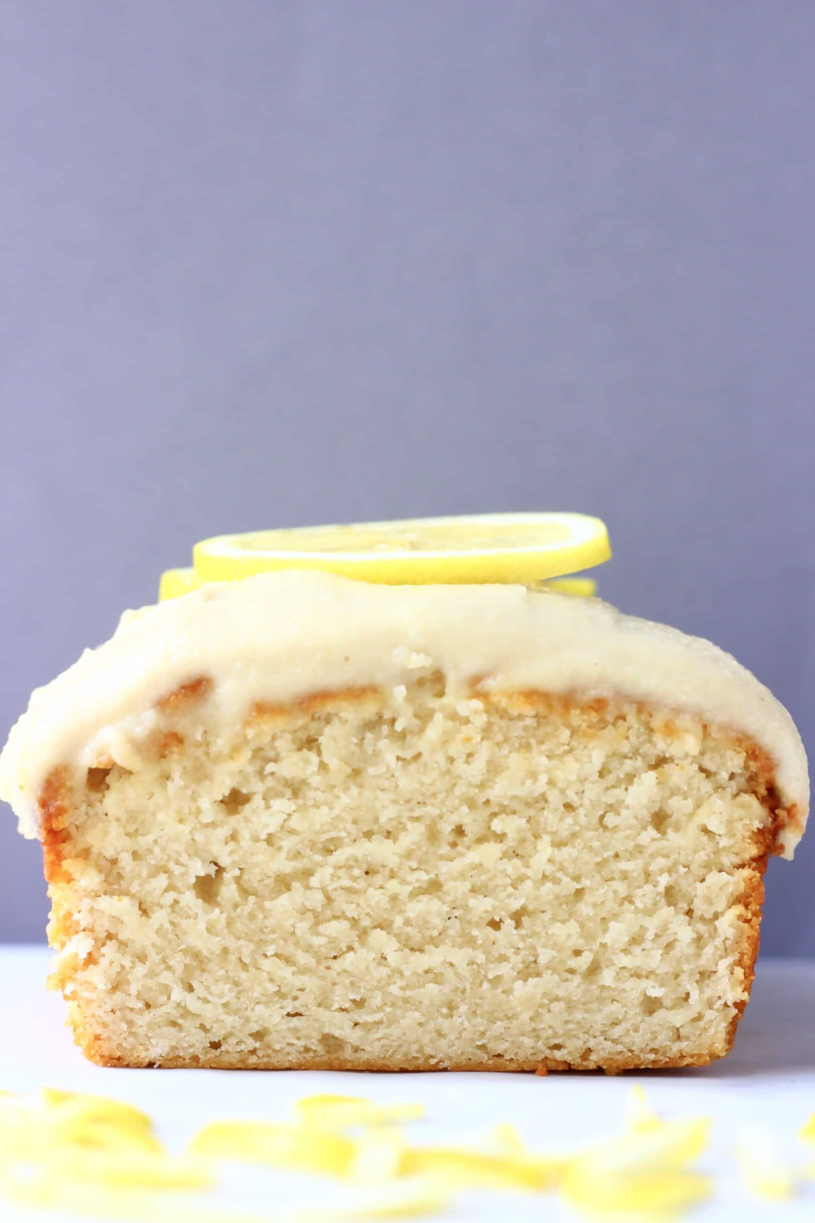 A sliced loaf of gluten-free vegan lemon bread topped with frosting and lemon slices