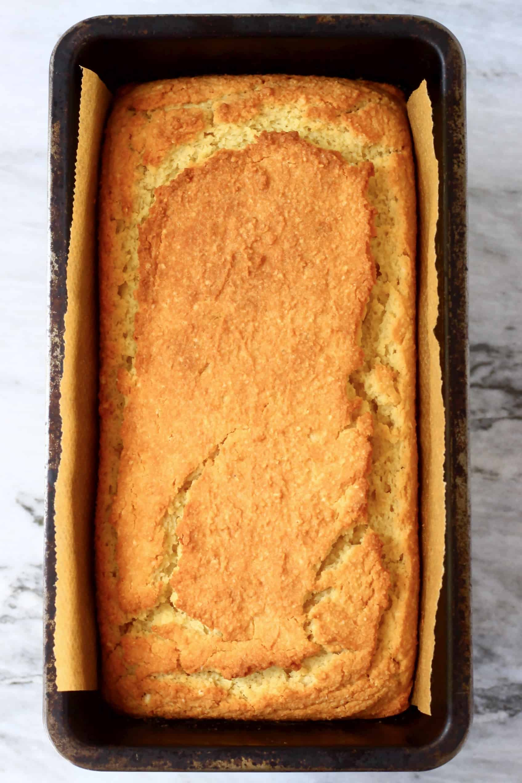 A loaf of gluten-free vegan orange pound cake in a loaf tin