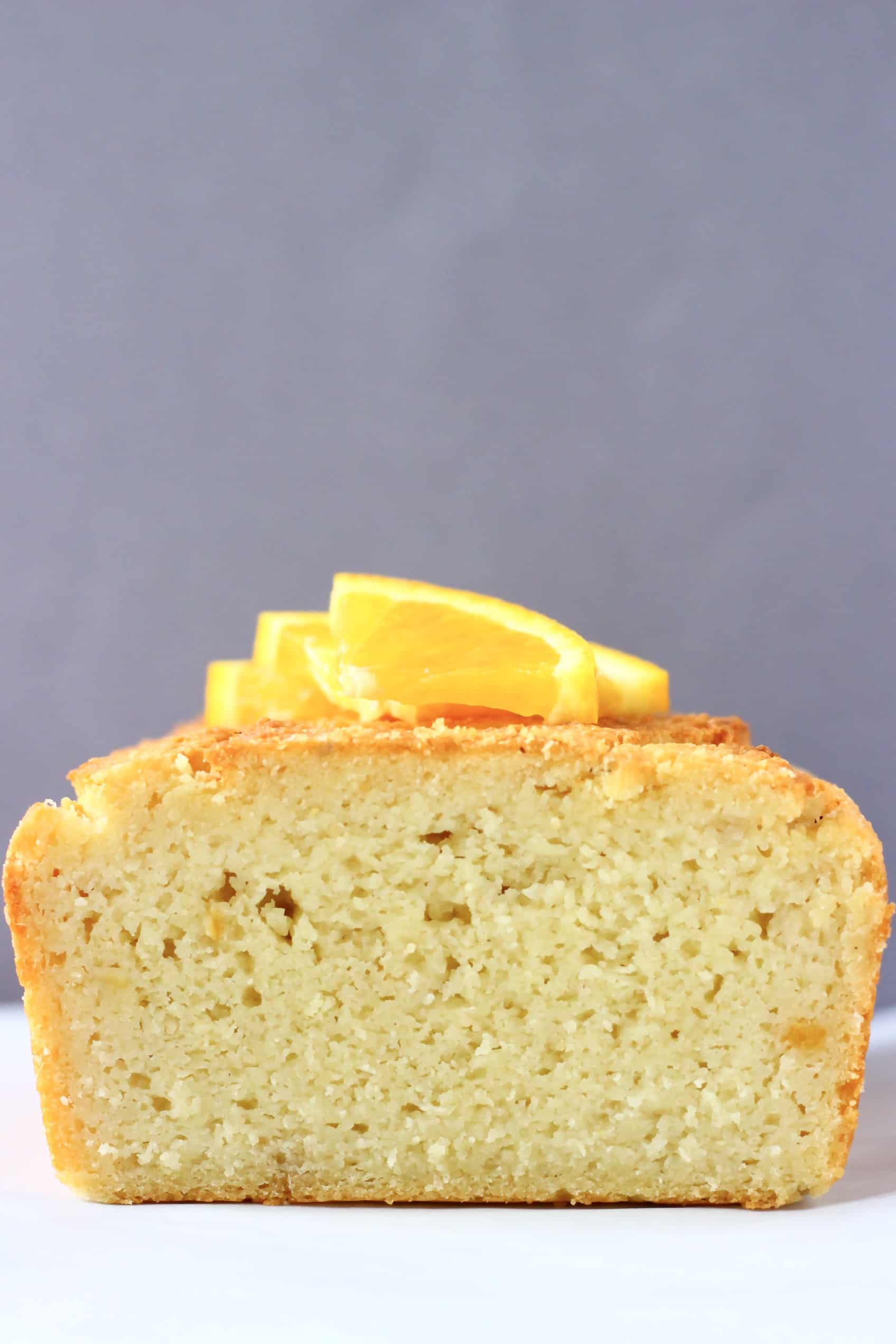 A sliced gluten-free vegan orange pound cake topped with orange wedges