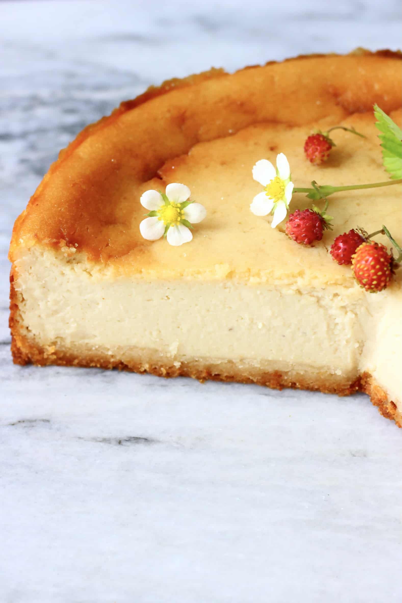 A sliced vegan baked cheesecake topped with wild strawberries and strawberry flowers