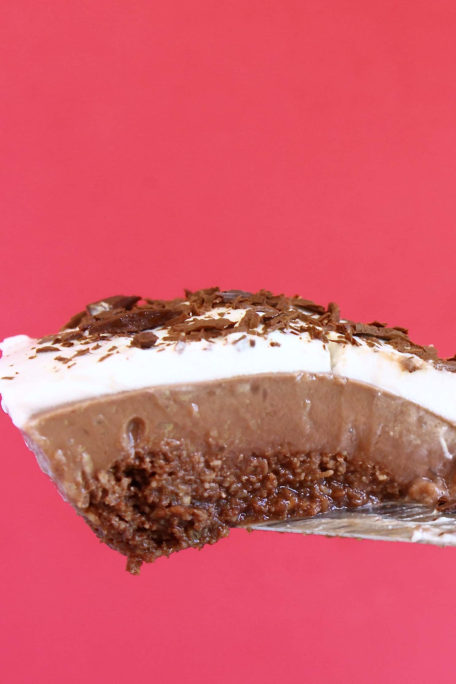 A slice of gluten-free vegan Mississippi mud pie with a chocolate base, chocolate custard and chocolate cream