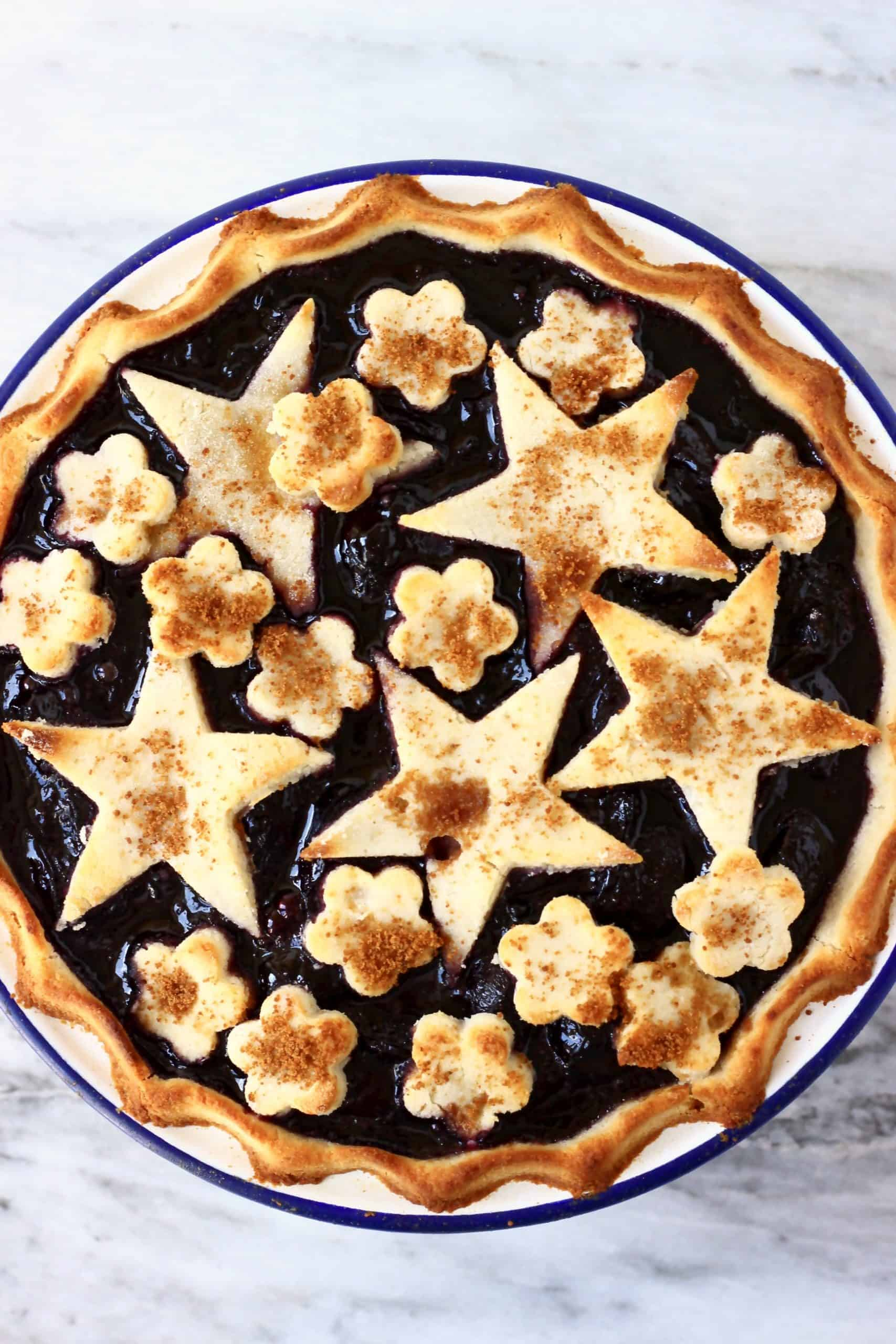 Gluten-free vegan cherry pie topped with pastry stars and flowers in a white pie dish