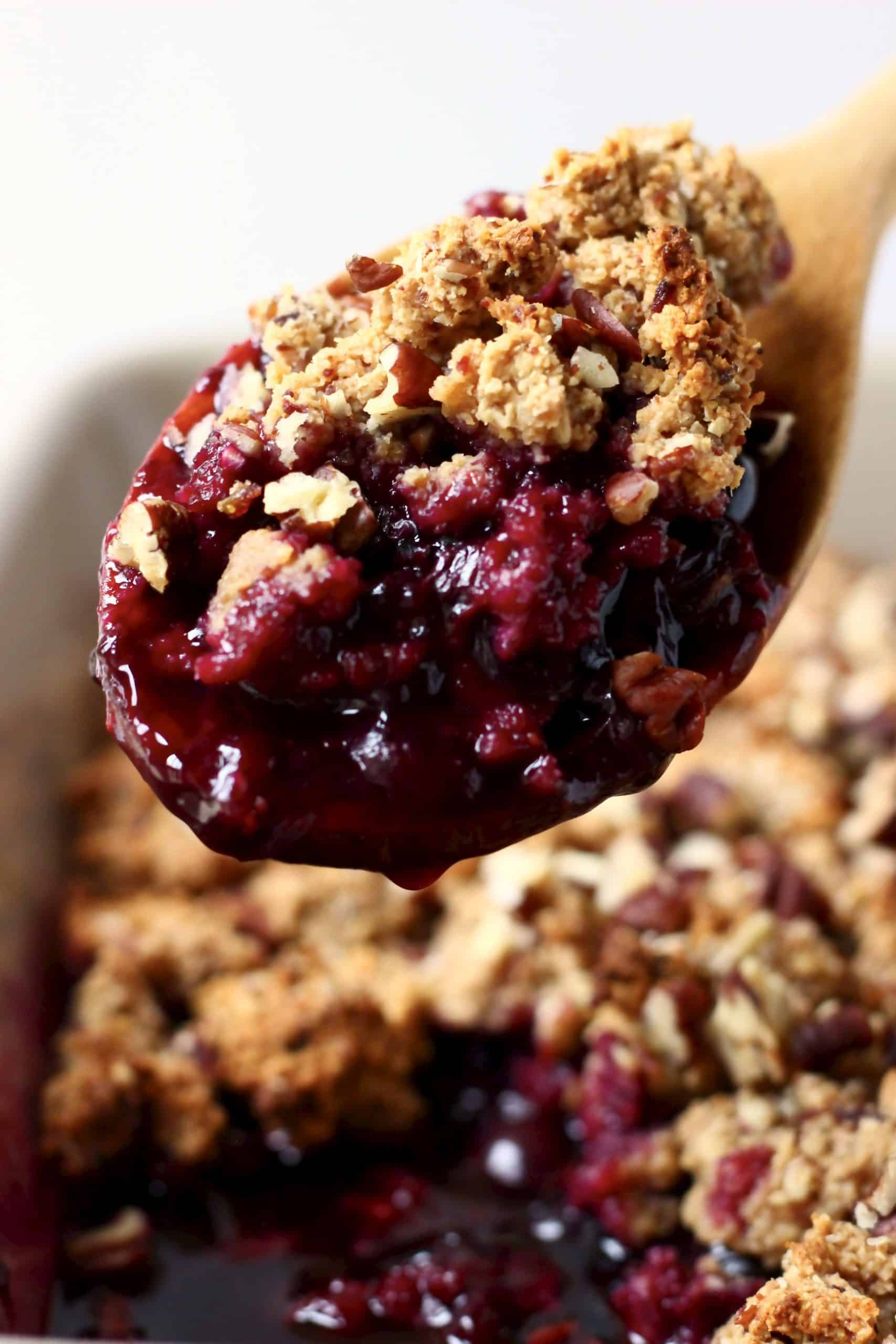 Blueberry crisp in a baking dish with a wooden spoon lifting up a mouthful
