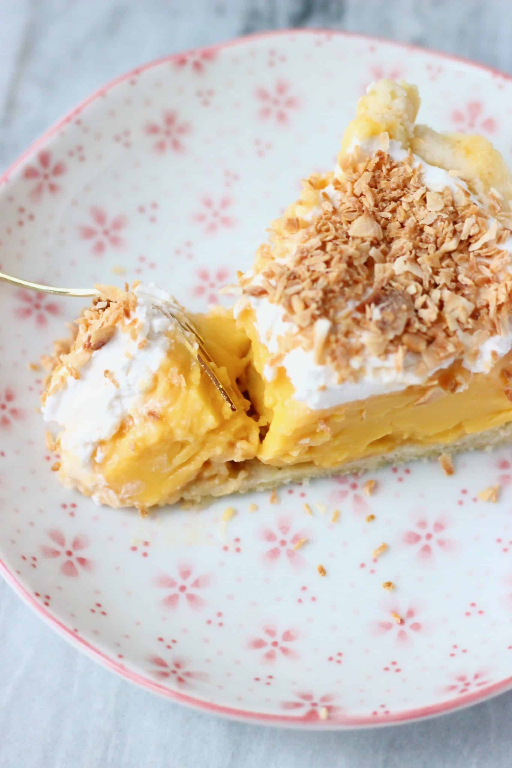 A slice of gluten-free vegan coconut cream pie with custard, cream and desiccated coconut