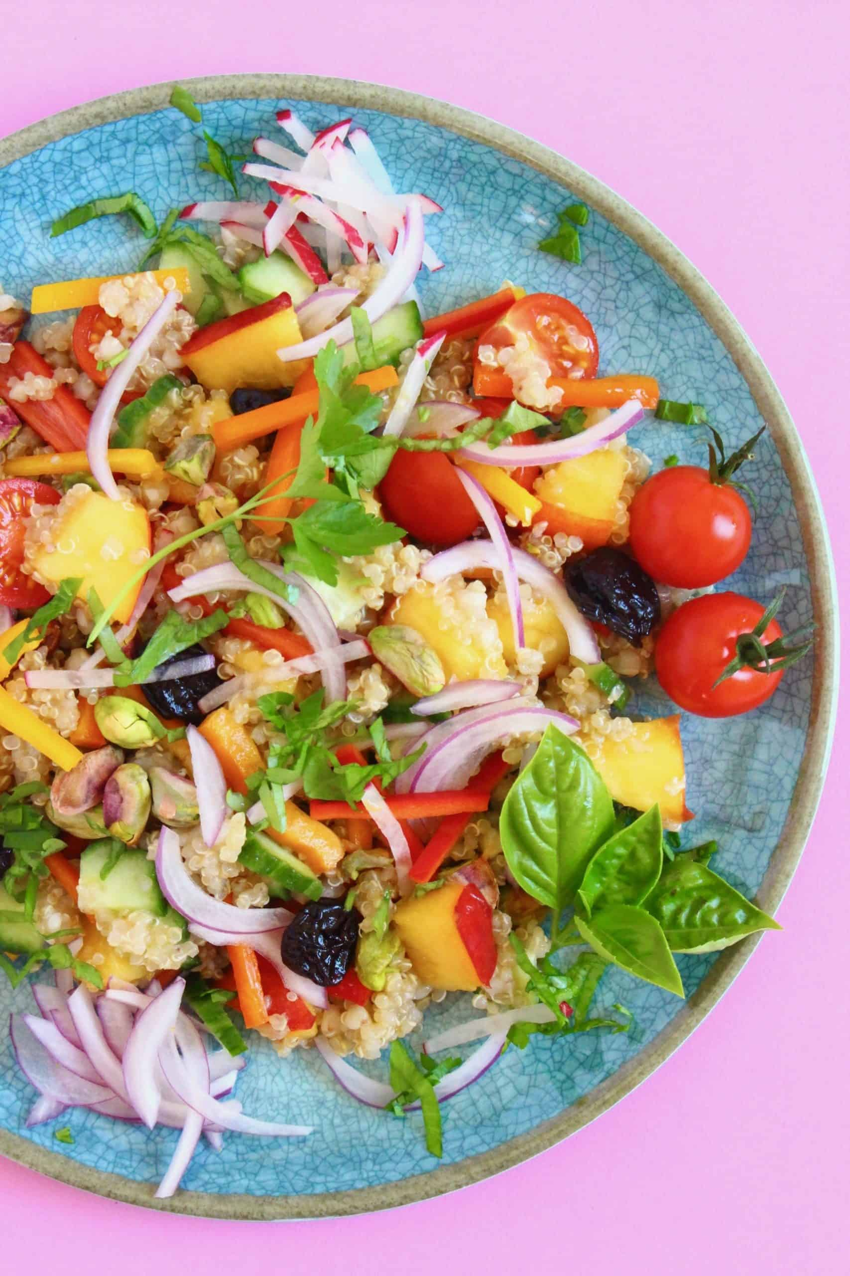 Quinoa tabbouleh with chopped nectarines, sliced red onion and herbs on a blue plate