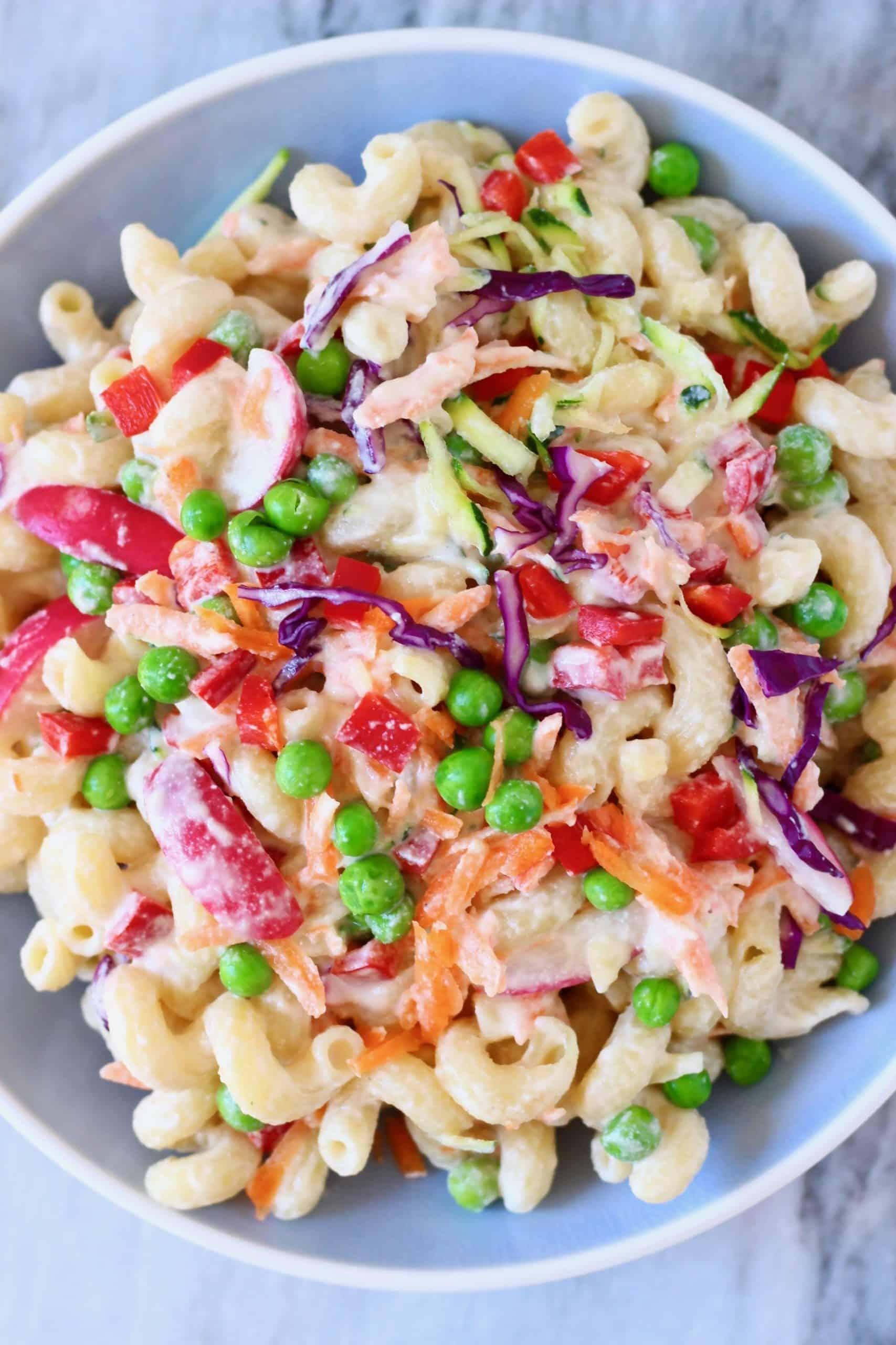 Vegan rainbow macaroni salad in a blue bowl