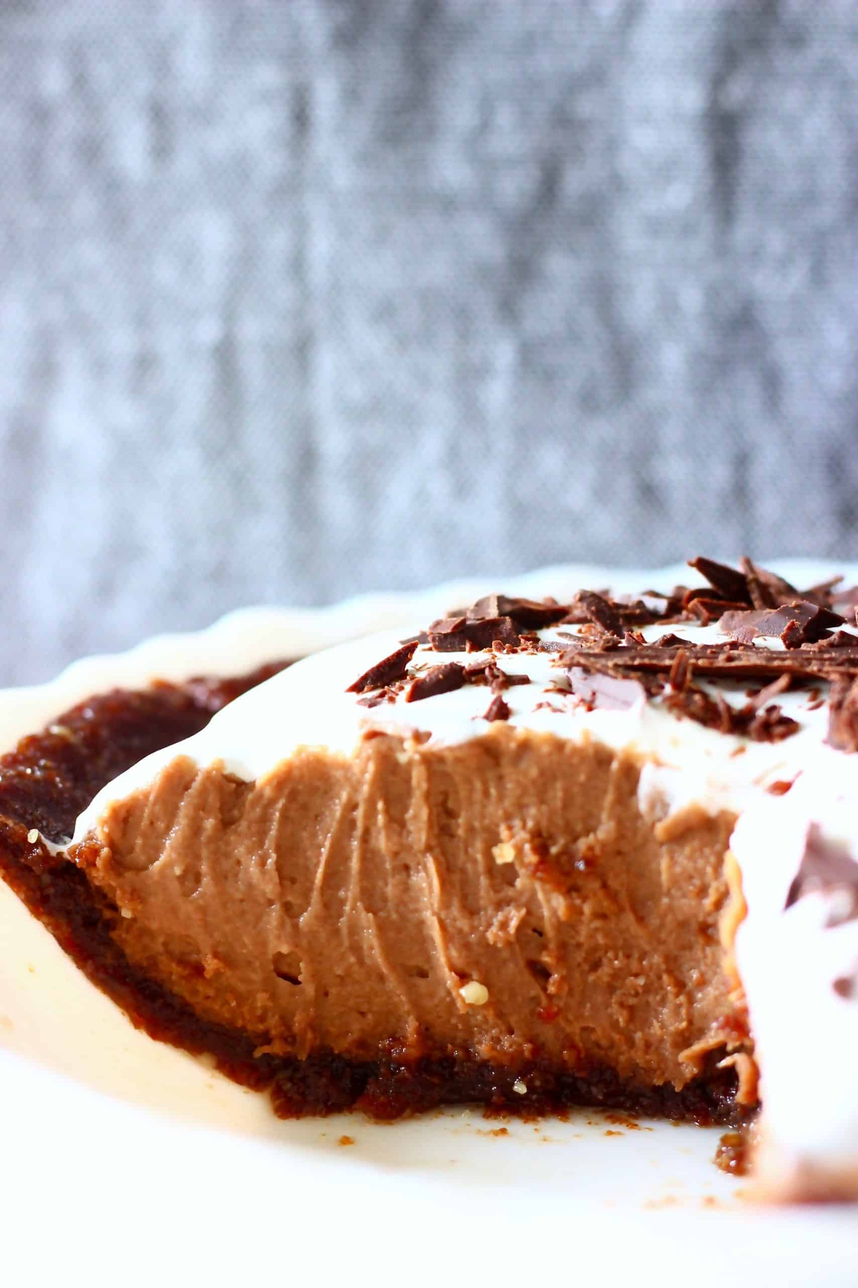 Vegan chocolate pie with chocolate pie crust, chocolate filling and white cream in a pie dish