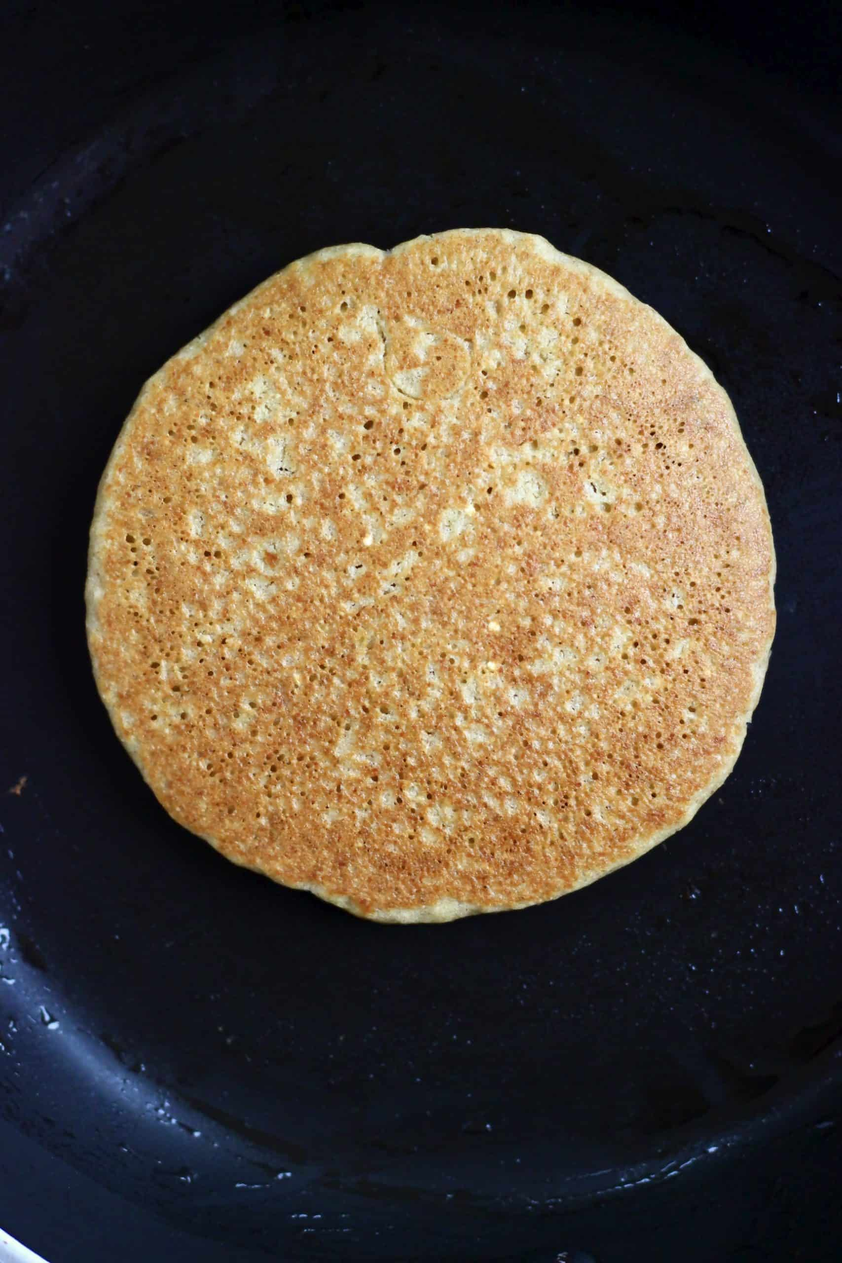 A golden brown quinoa pancake in a black frying pan