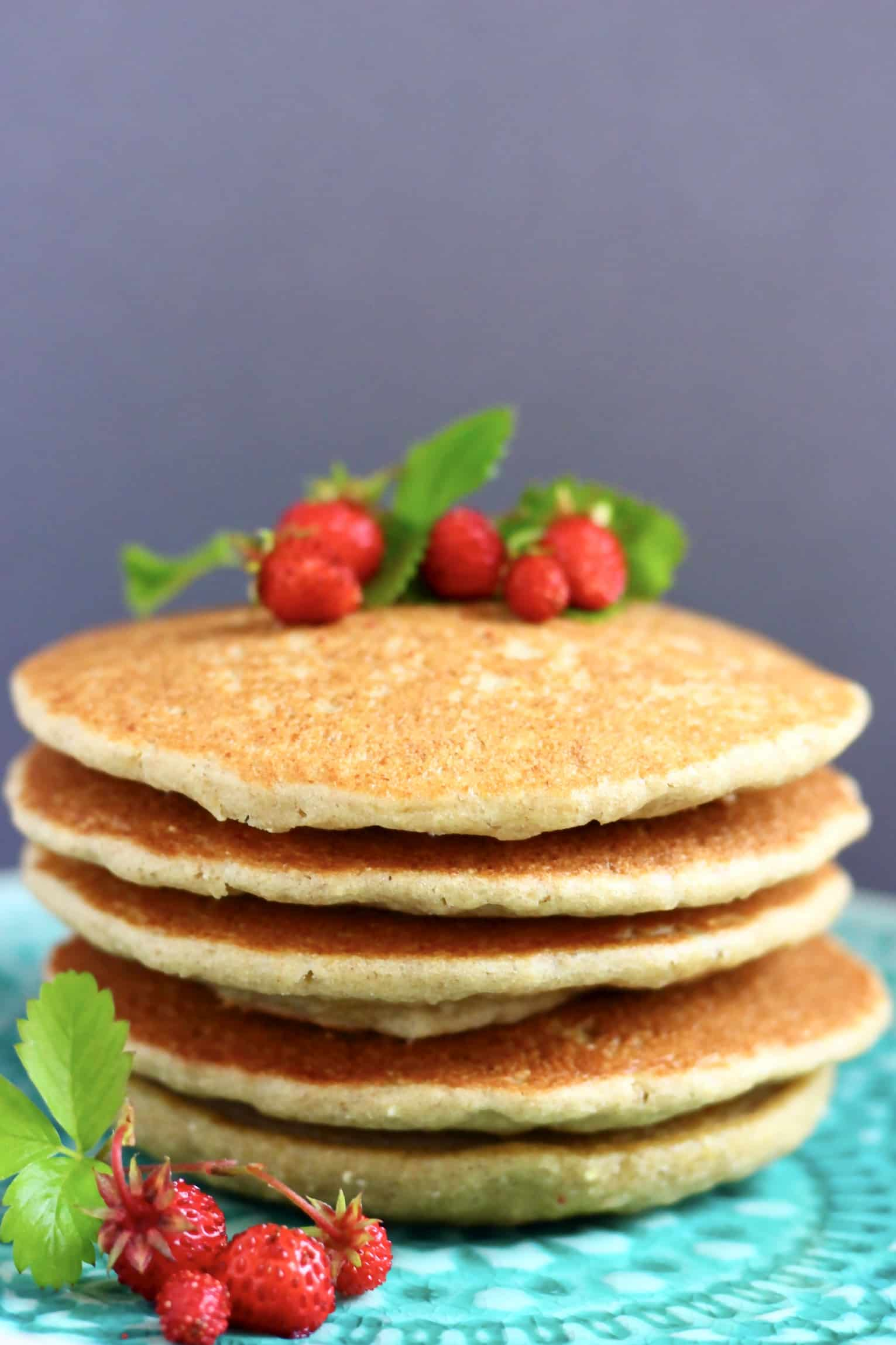 A stack of five quinoa pancakes topped with wild strawberries on a plate
