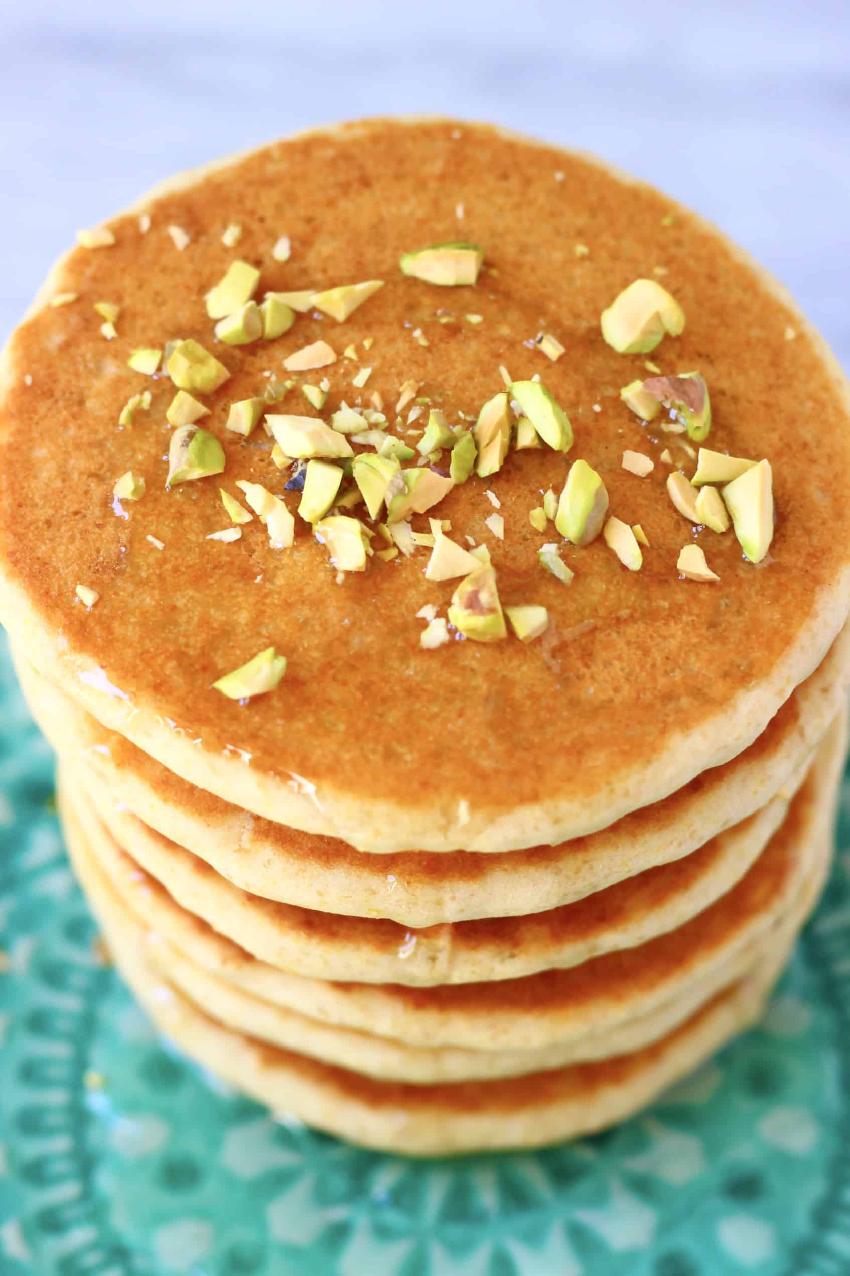 A stack of flaxseed pancakes on a plate topped with syrup and chopped pistachios