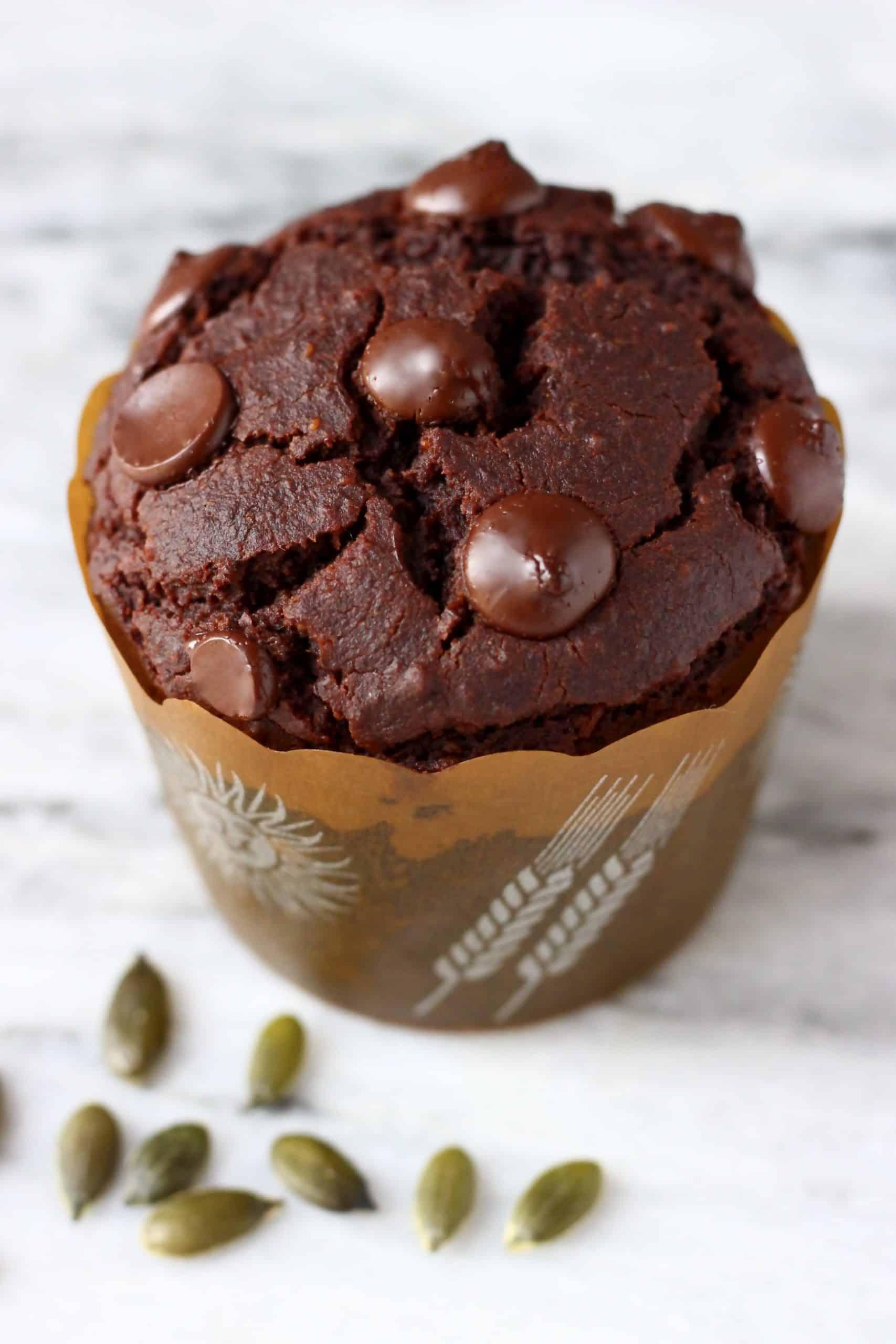A gluten-free vegan chocolate pumpkin muffin in a brown muffin case