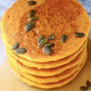 A stack of gluten-free vegan pancakes on a plate topped with syrup and pumpkin seeds