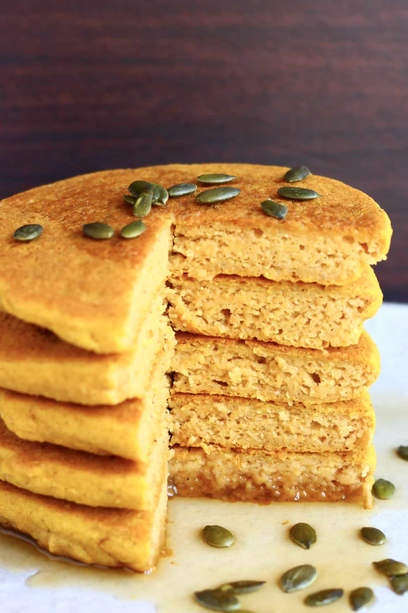 A stack of sliced gluten-free vegan pumpkin pancakes on a plate