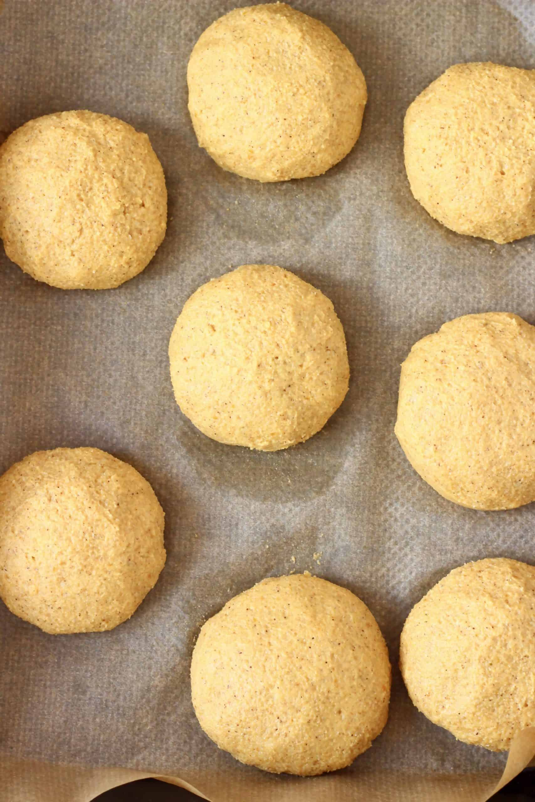 Eight raw gluten-free vegan pumpkin cookies on a baking tray