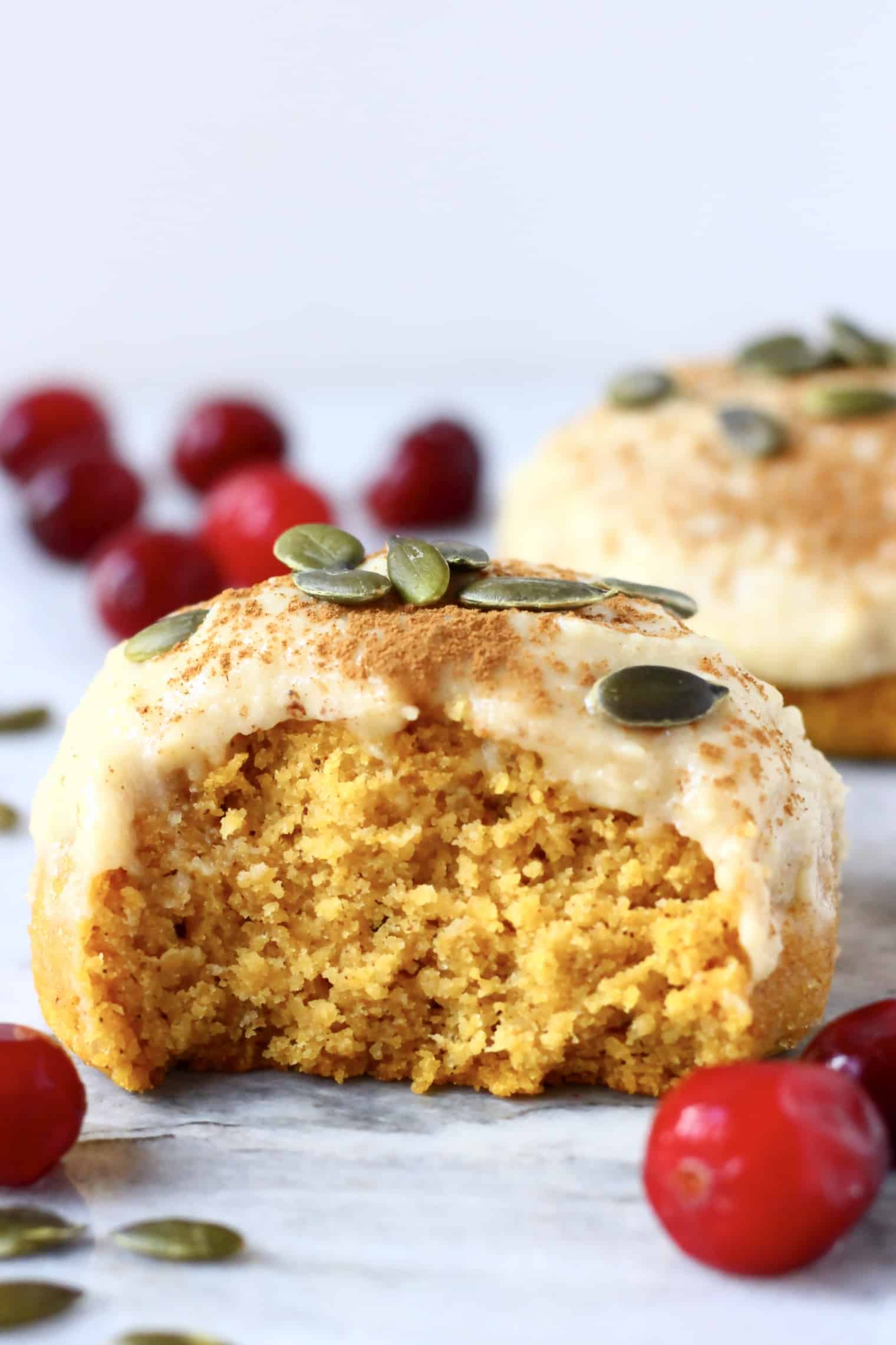 A halved gluten-free vegan pumpkin cookie topped with white frosting and pumpkin seeds
