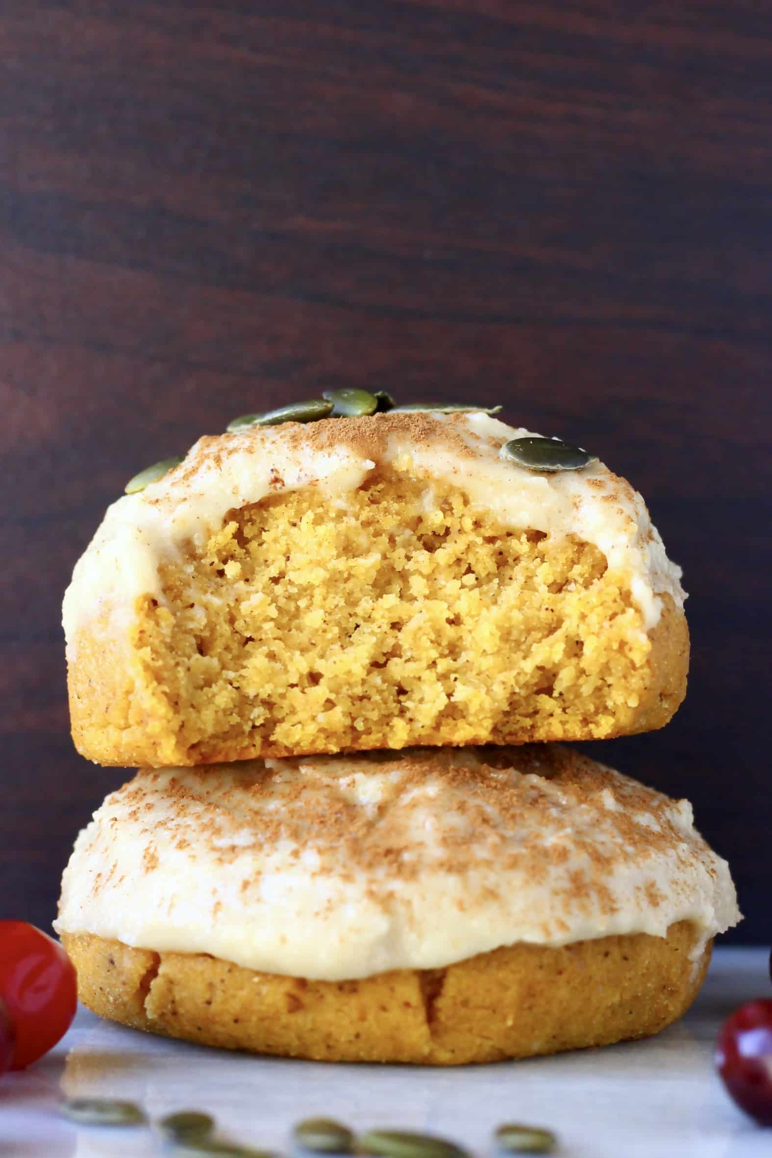 Two gluten-free vegan pumpkin cookies with frosting stacked on top of each other, one cut in half