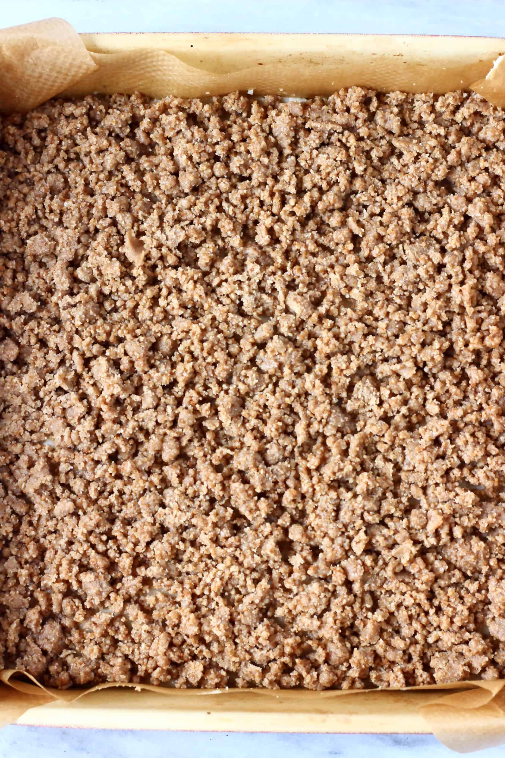Raw vegan coffee cake batter with raw streusel topping in a square baking tin