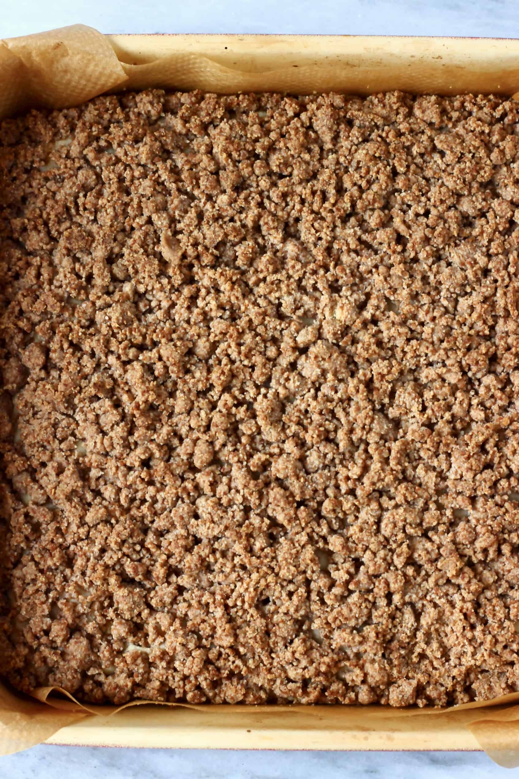 Vegan coffee cake with streusel topping in a square baking tin