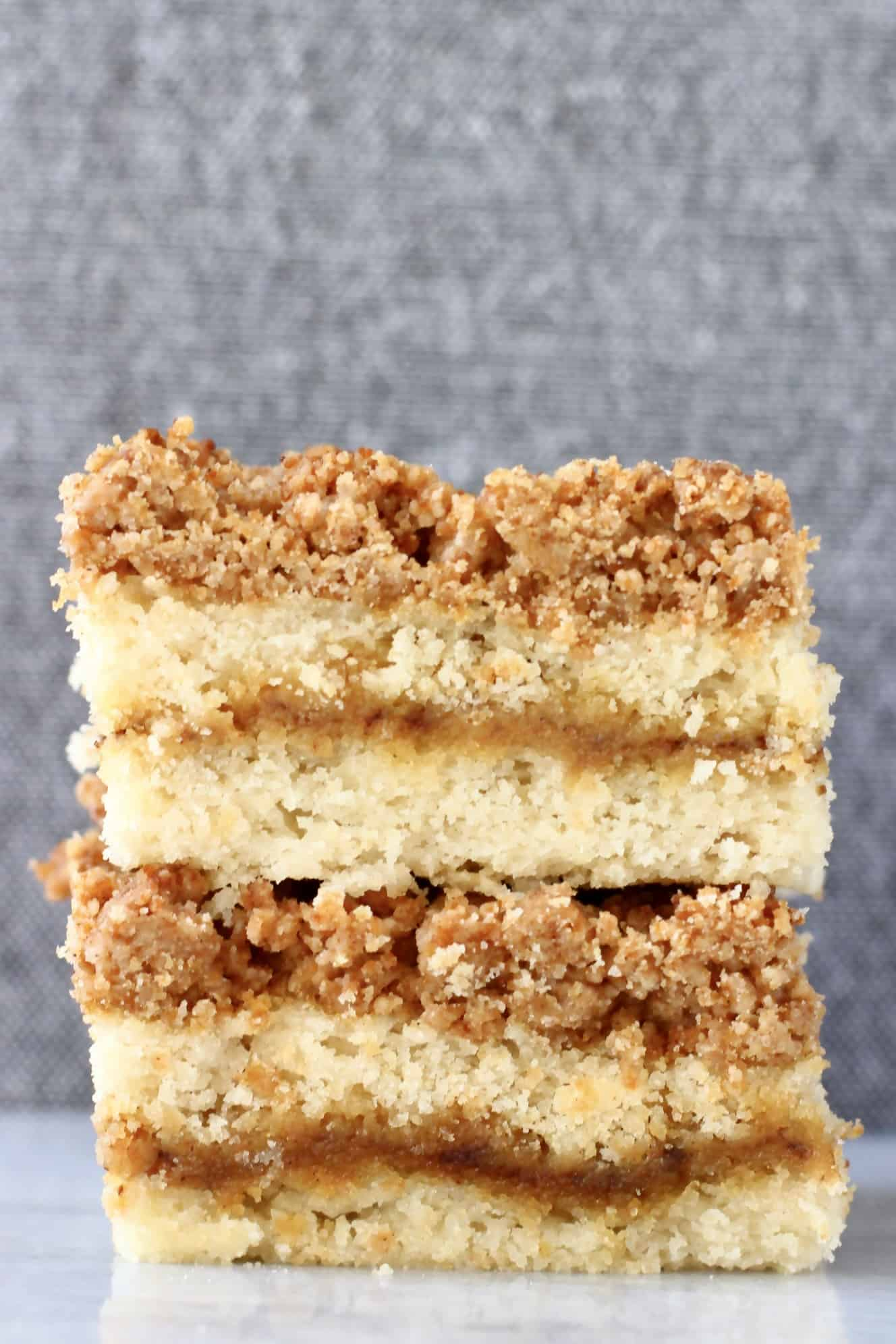 Two square slices of vegan coffee cake with streusel topping stacked on top of each other