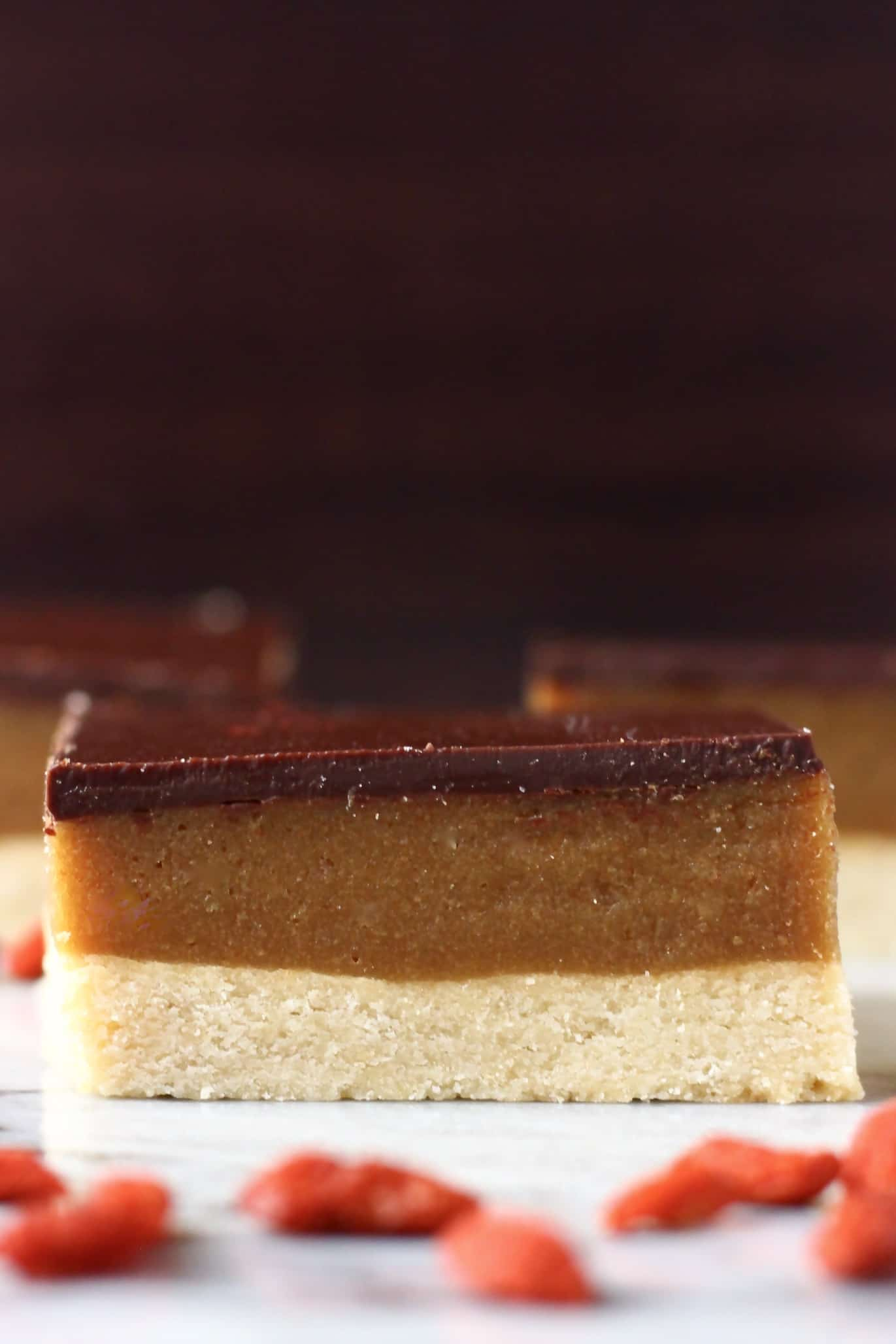 Three millionaire shortbread squares and goji berries on marble