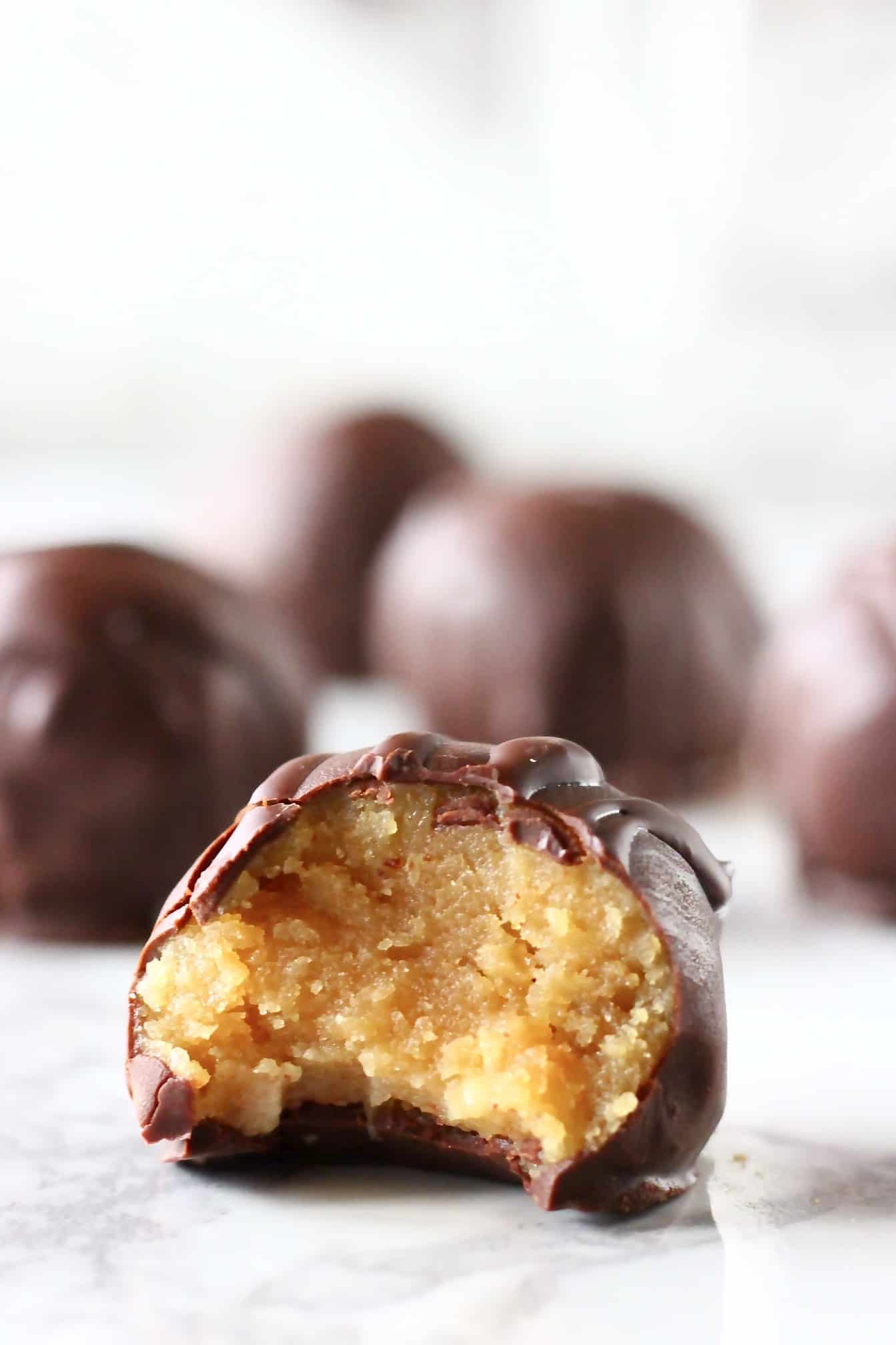 Chocolate-covered peanut butter balls with a bite taken out of one
