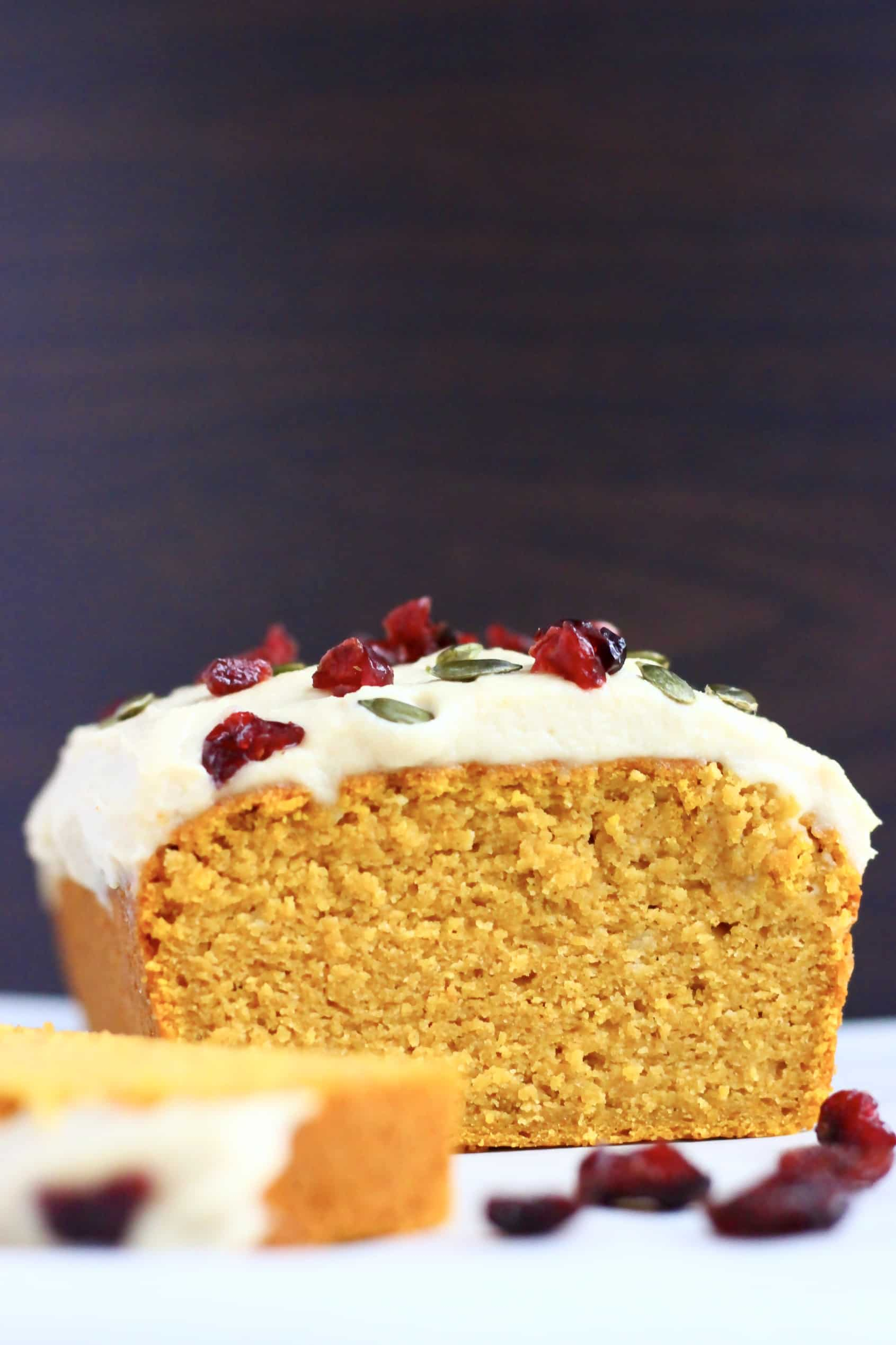 A sliced gluten-free vegan pumpkin loaf cake topped with cream cheese frosting, dried cranberries and pumpkin seeds