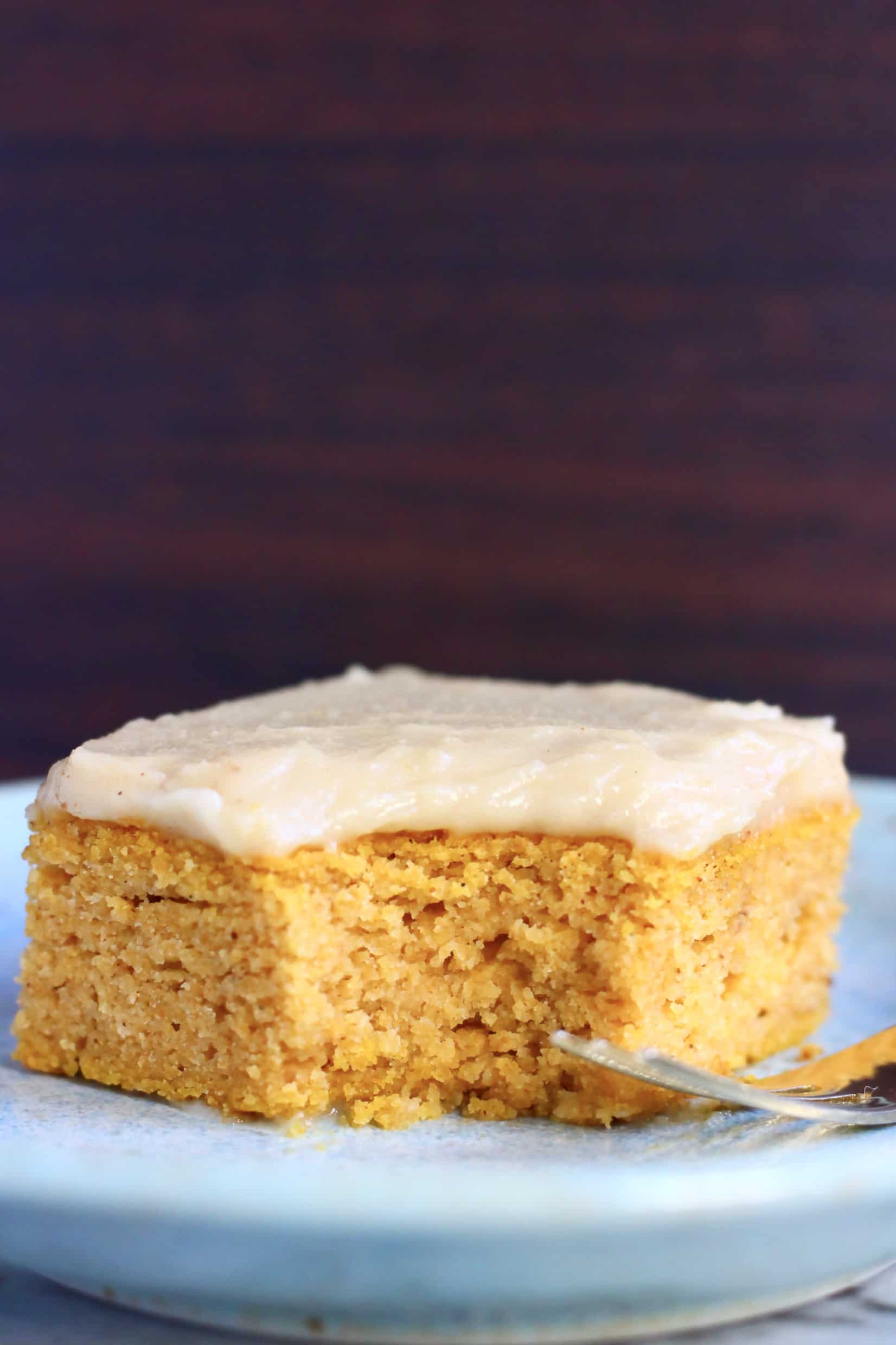 A square of gluten-free vegan pumpkin bars topped with frosting with a mouthful taken out of it on a  plate with a fork