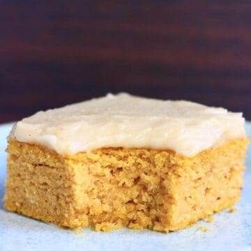 A square of gluten-free vegan pumpkin bars topped with frosting with a mouthful taken out of it on a blue plate