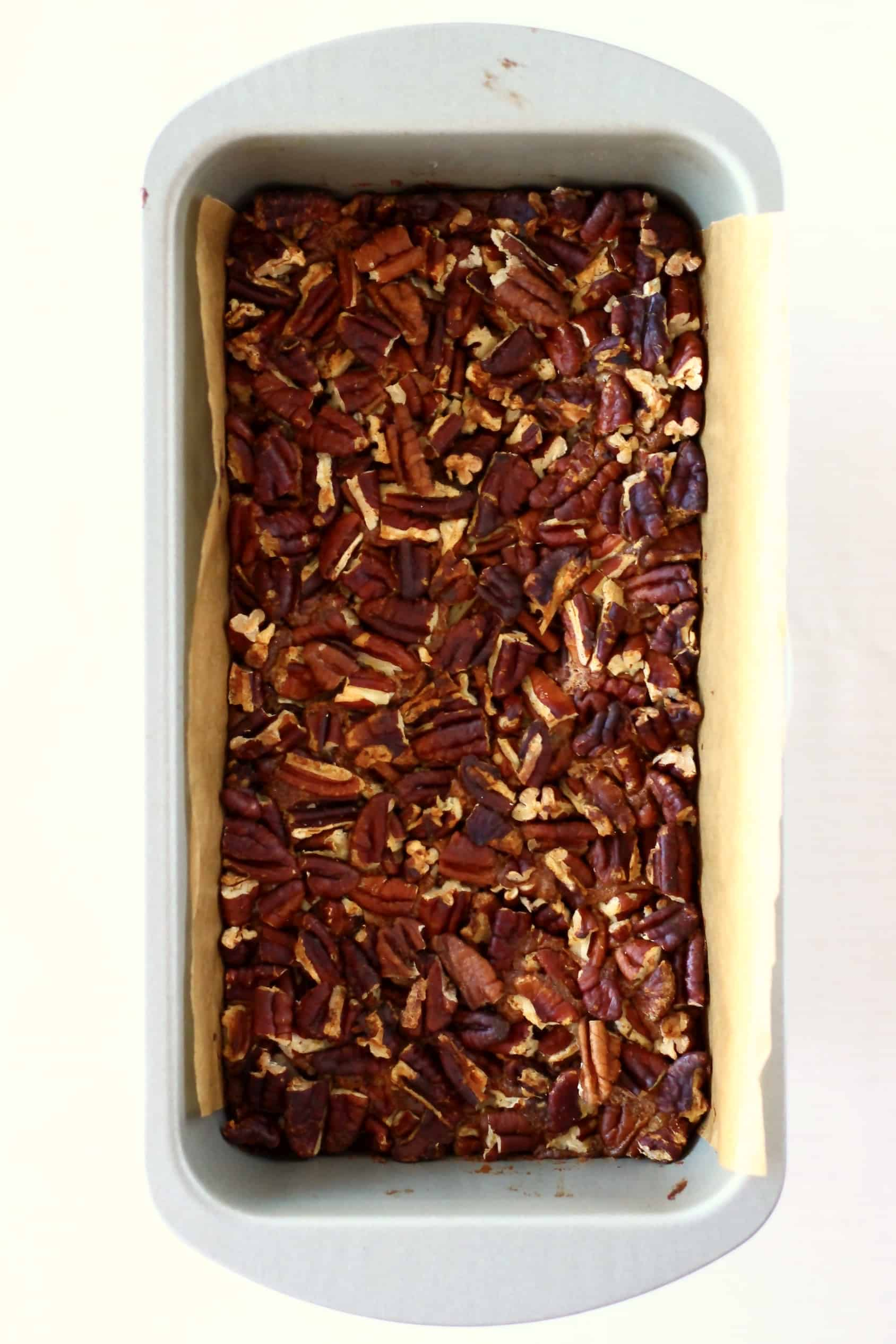 Baked vegan pecan pie bars in a loaf tin lined with baking paper