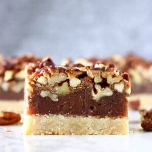 Three vegan pecan pie bars with a pie crust base, date caramel filling and topped with pecans