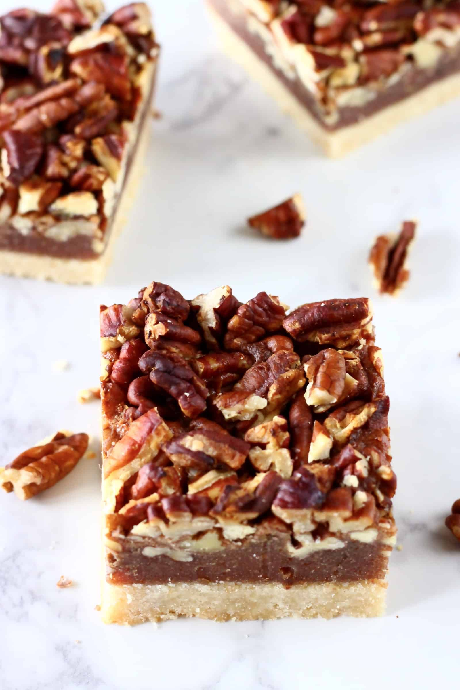 Three square vegan pecan pie bars on a marble background