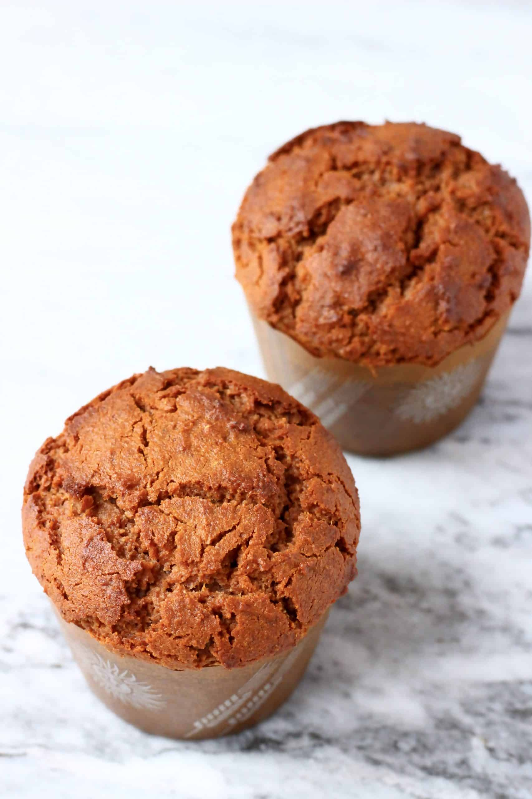 Two gluten-free vegan gingerbread muffins in brown muffin cases