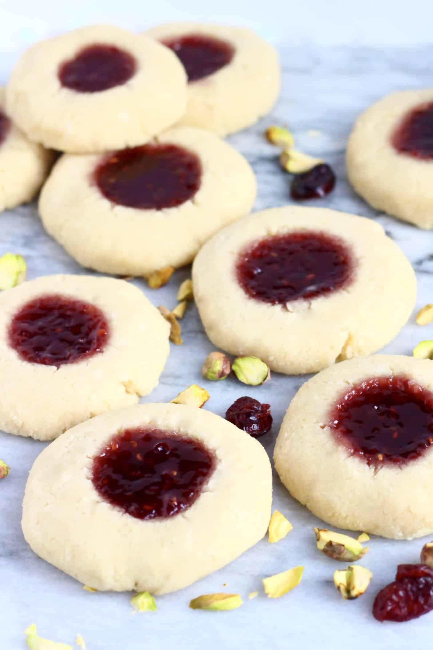 Nine gluten-free vegan thumbprint cookies filled with raspberry jam on a marble background