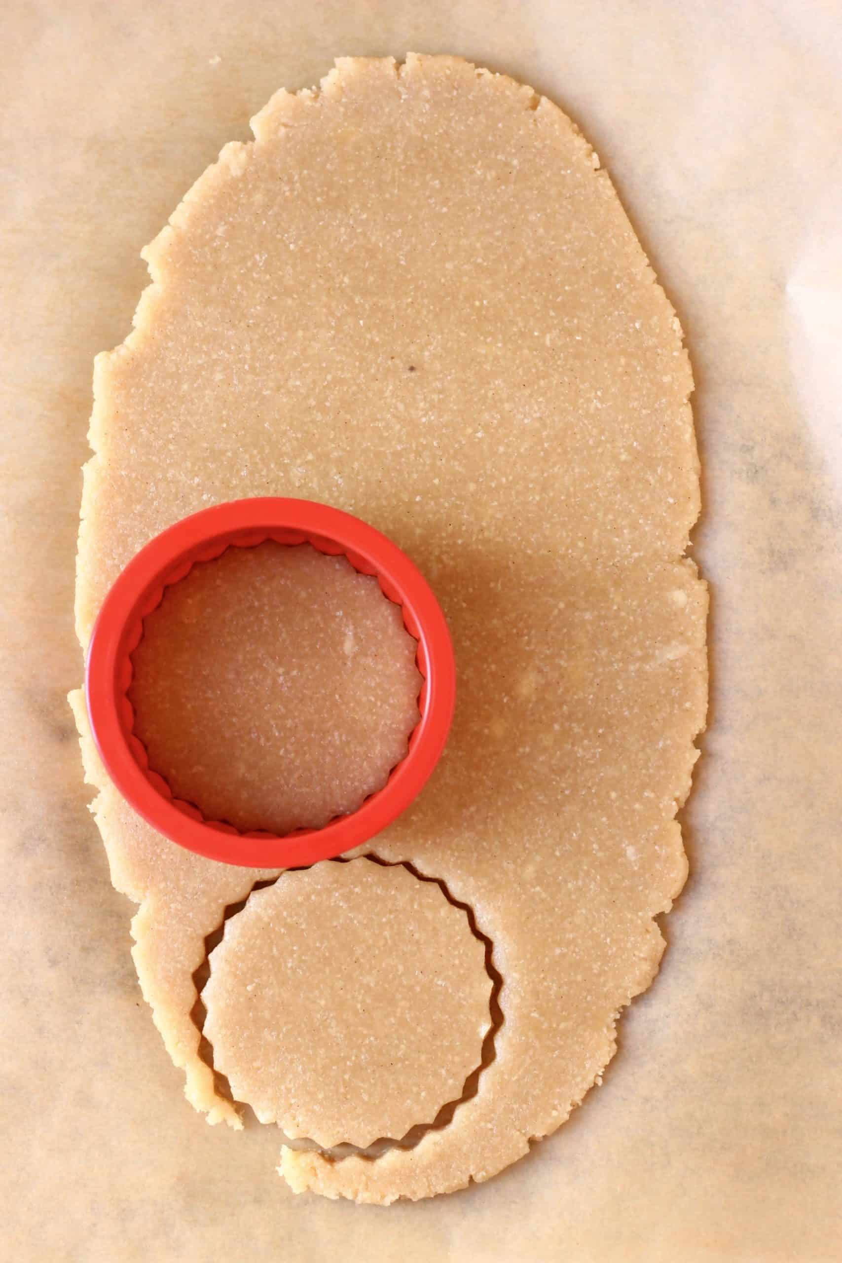 Raw gluten-free vegan linzer cookie dough rolled out on a sheet of baking paper with a circular cookie cutter cutting out shapes