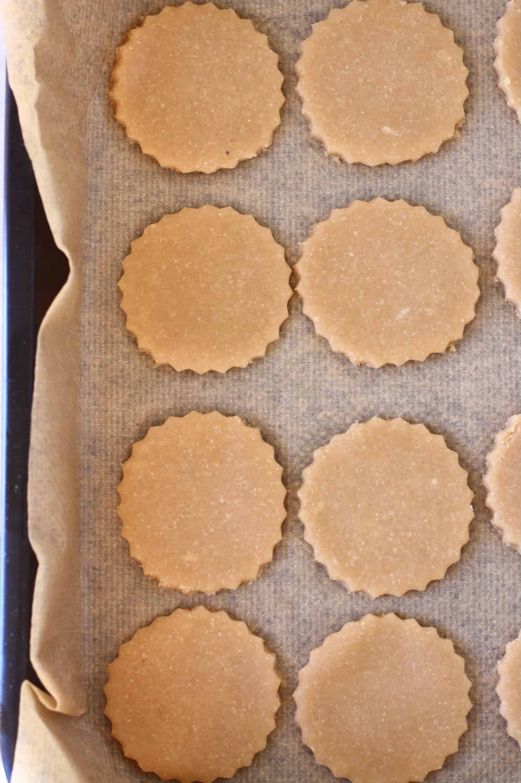 Eight raw gluten-free vegan linzer cookie circles on a baking tray lined with baking paper