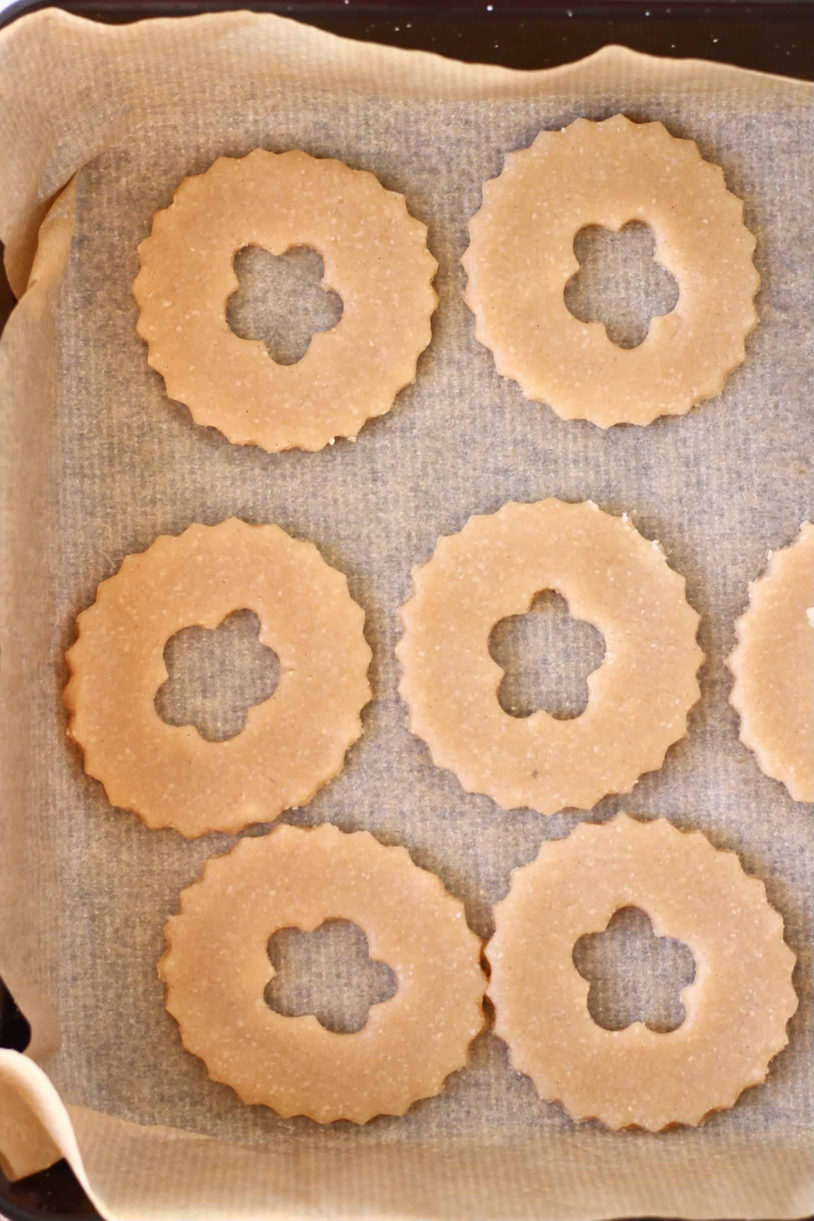 Six raw gluten-free vegan linzer cookie circles with flower-shaped windows on a baking tray lined with baking paper