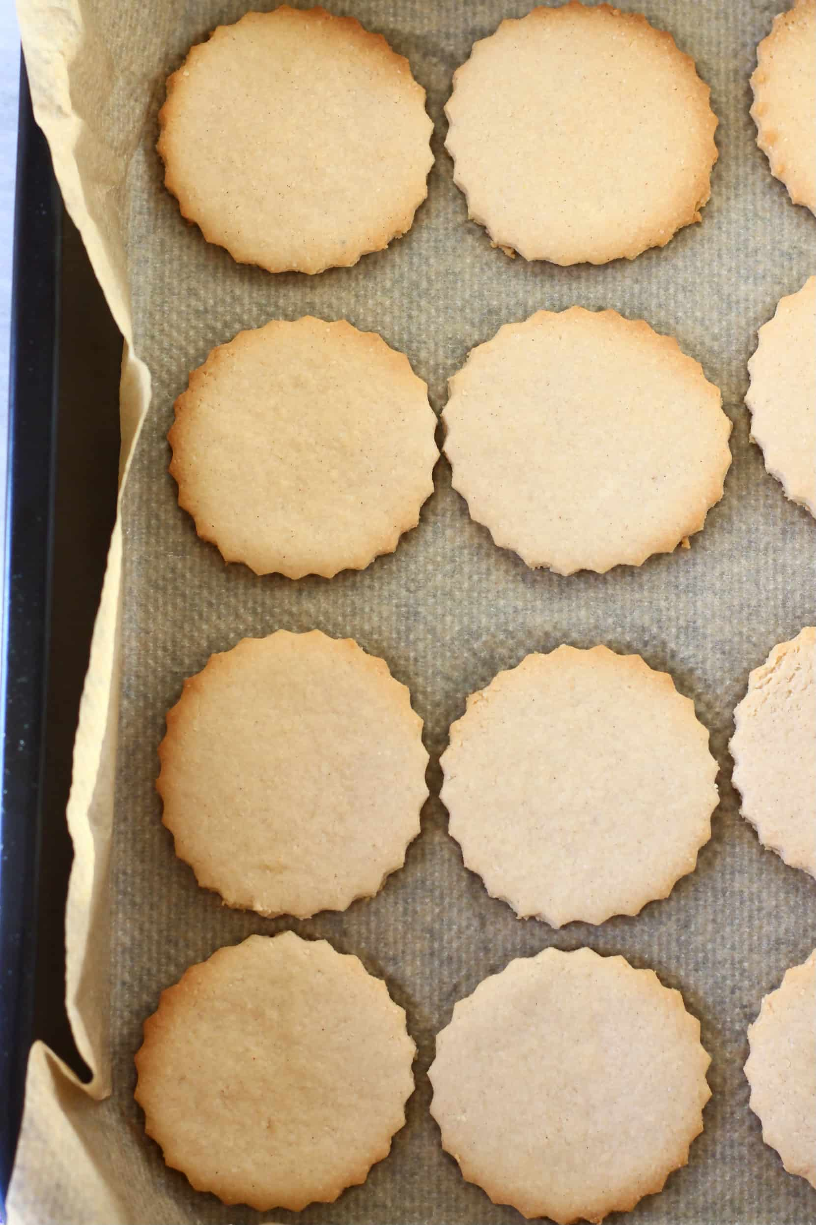 Eight gluten-free vegan linzer cookie circles on a baking tray lined with baking paper