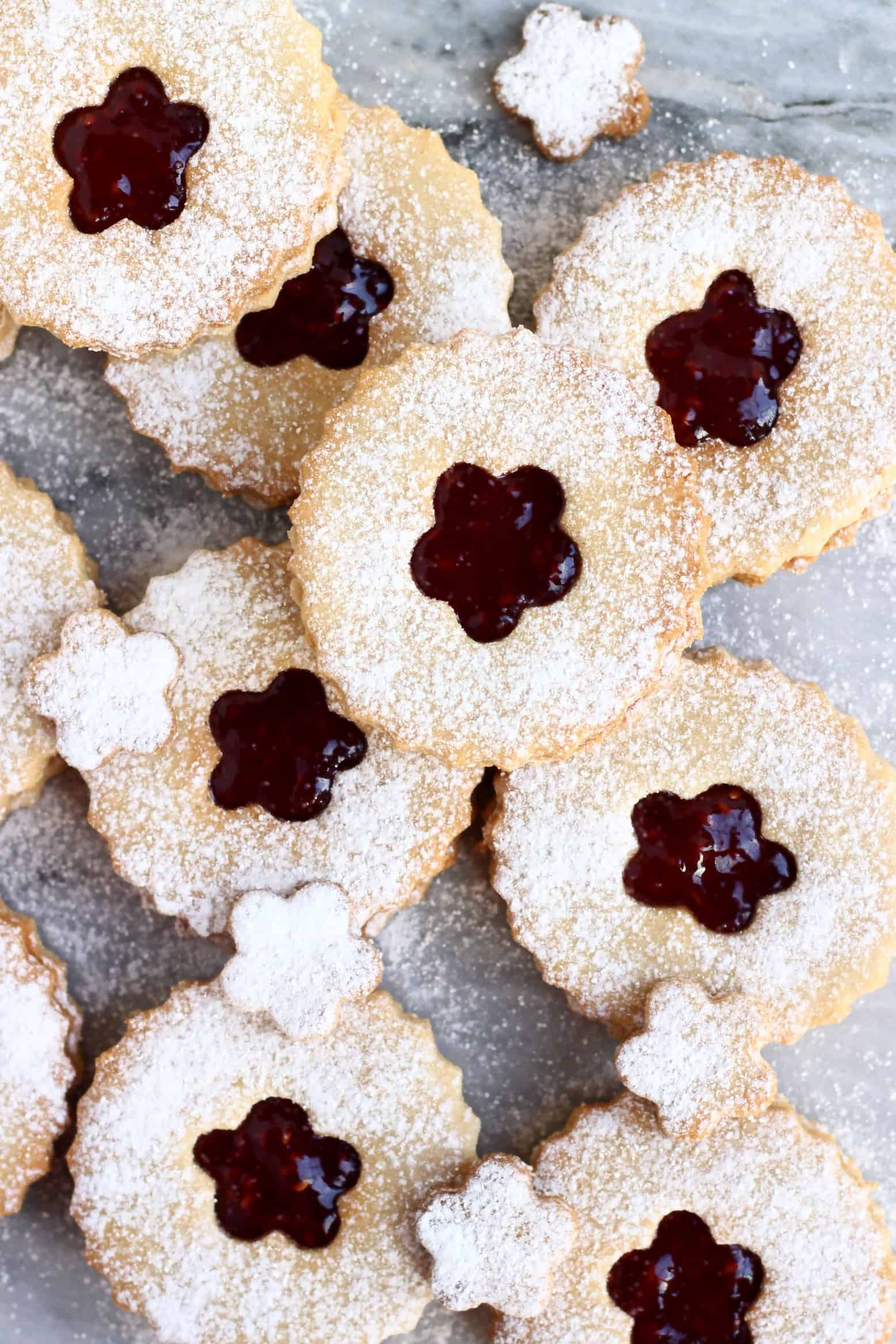 Nine gluten-free vegan linzer cookies filled with raspberry jam